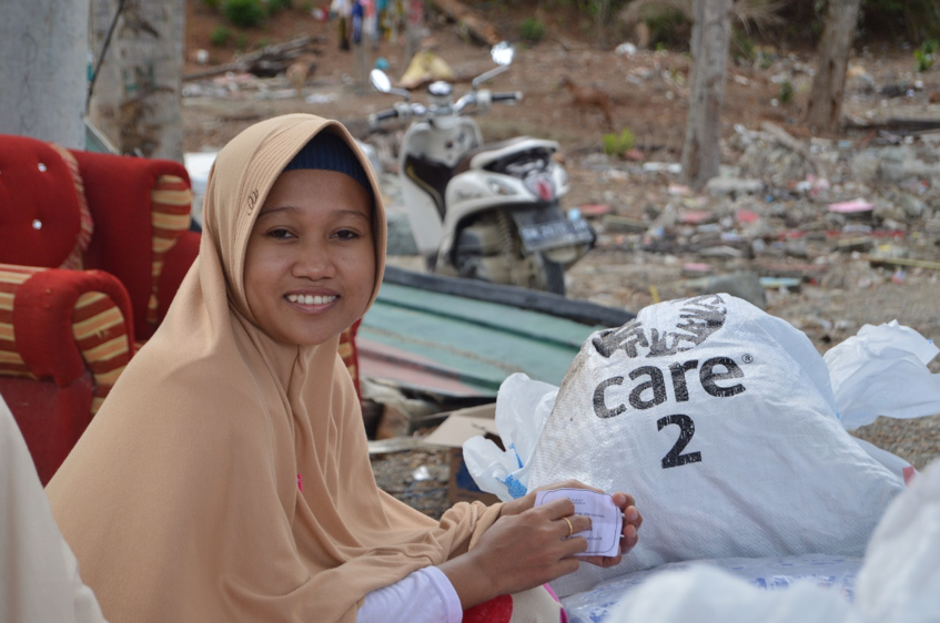 Above: A woman in Donggala District, waiting to bring home care packages. tPhoto credit: CARE.