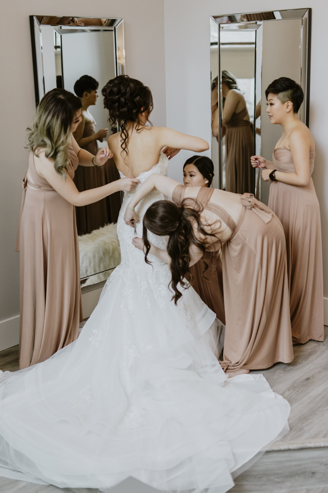 bride getting help putting her dress put on