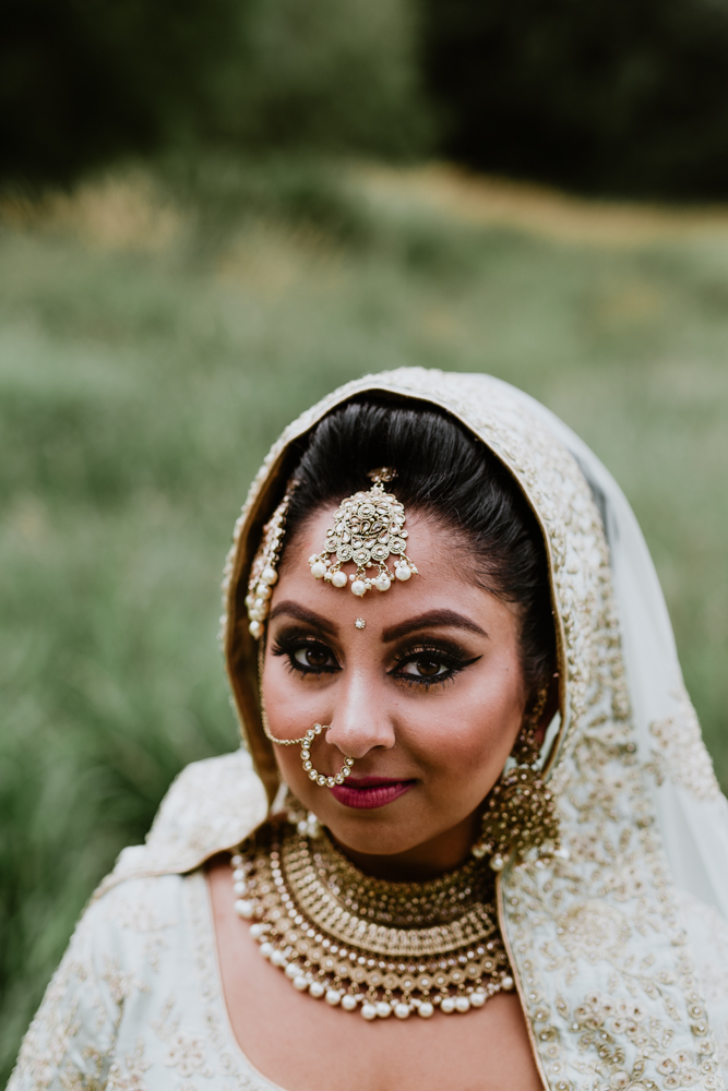 indian bride standing in the middle of a field