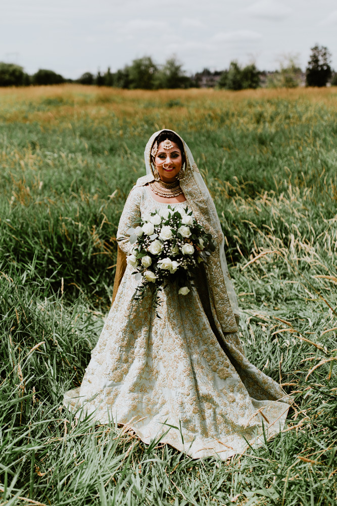 Indian bride standing in field