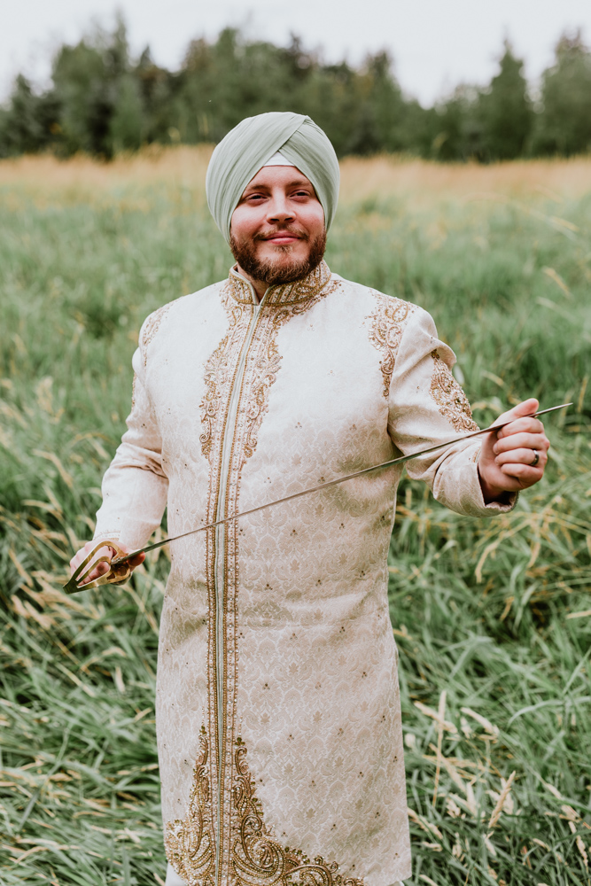 indian groom standing in field.jpg