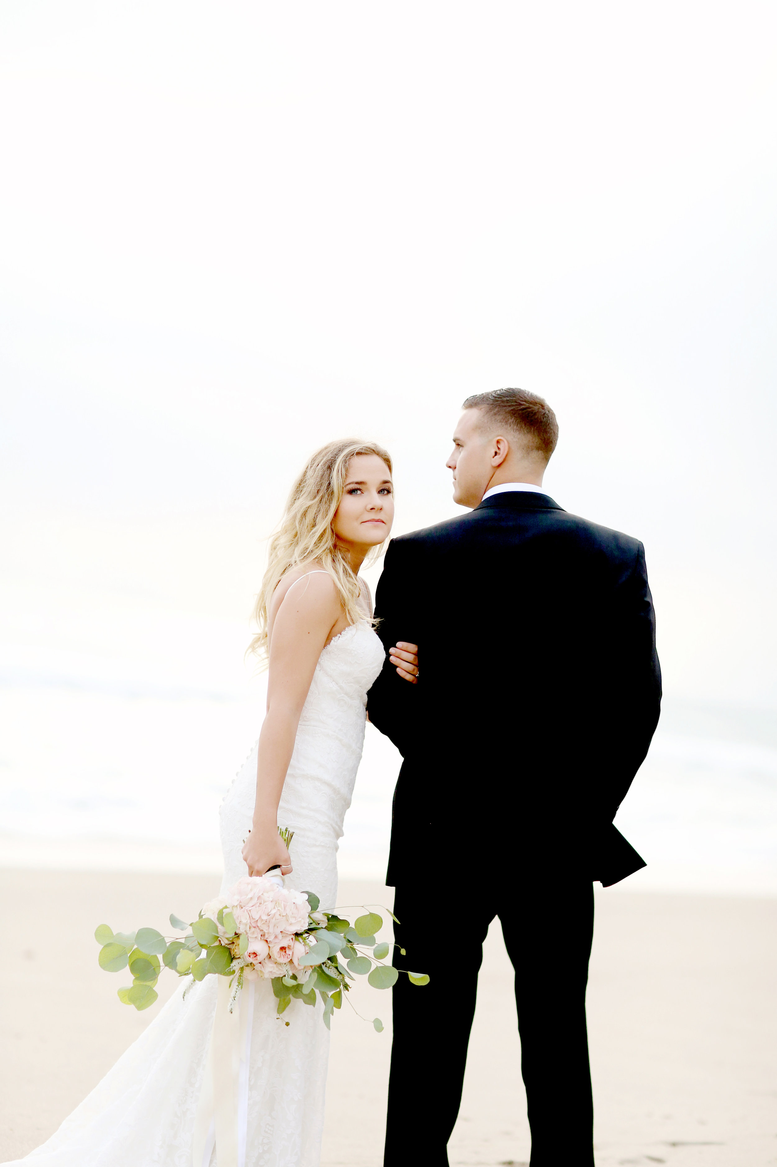 Bride and groom at the beach in San Clemente, Orange County. Bride is holding a pink bouquet by  Bleudog Floral