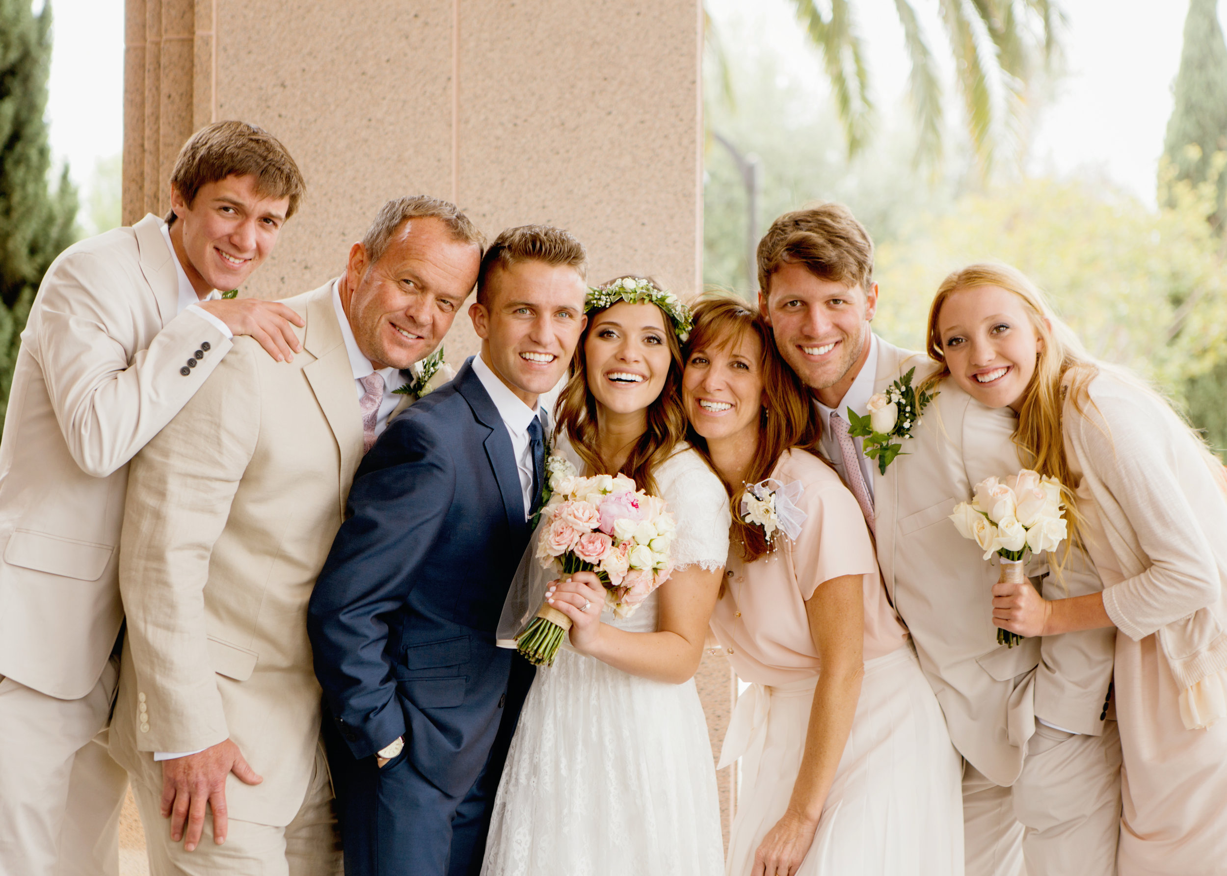 A wedding photo of the entire family. Bride holding a pink bouquet made by Bleudog Floral. Lovely family portrait.