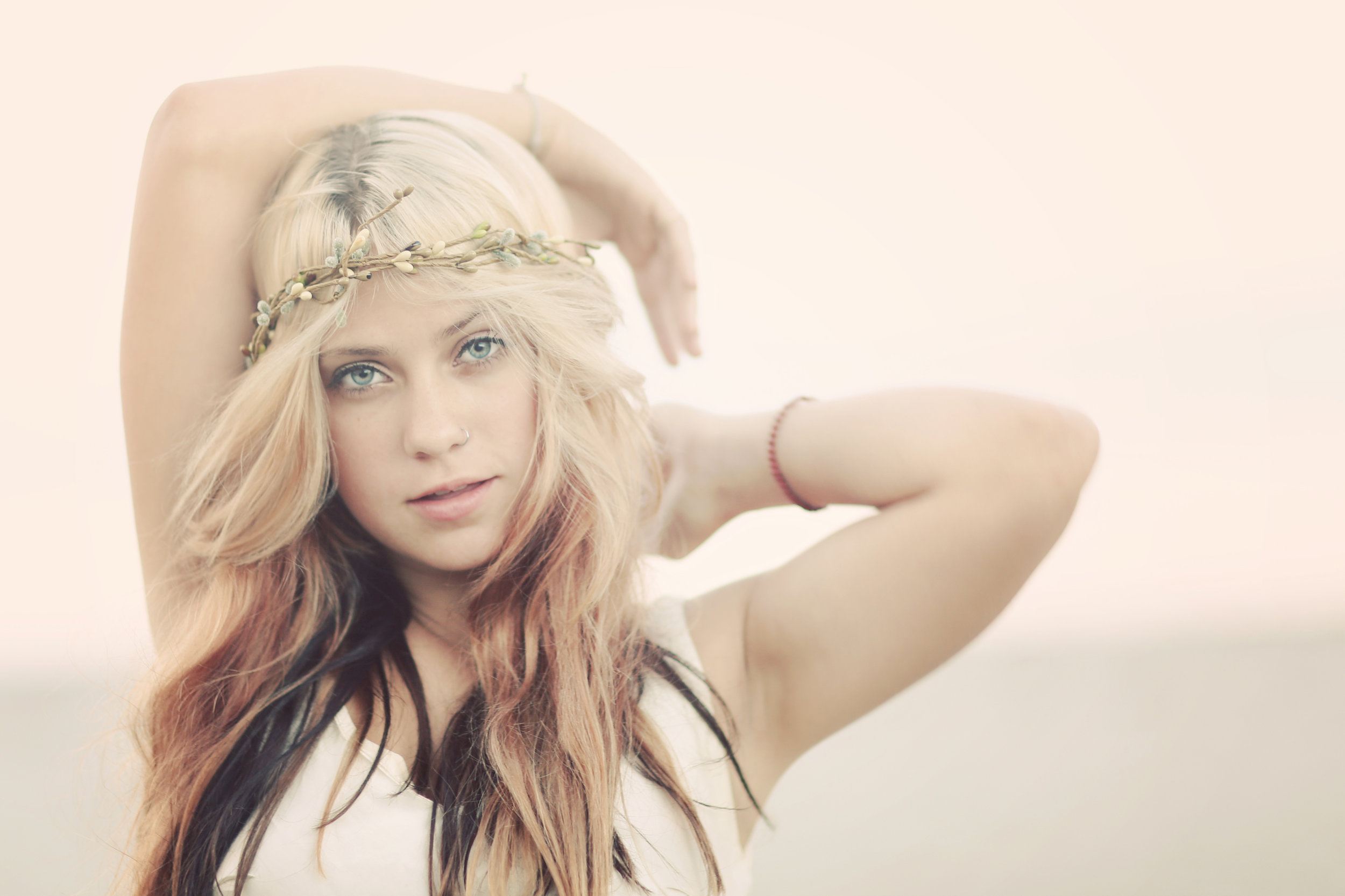 Young Orange County girl at the beach posing for a portrait. Long hair, blue eyes.