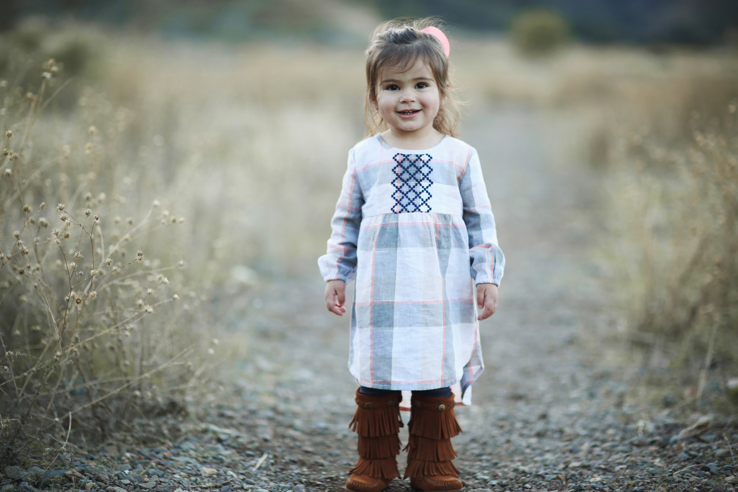 Toddler portrait in fringe moccasin boots standing in a field in Orange County.
