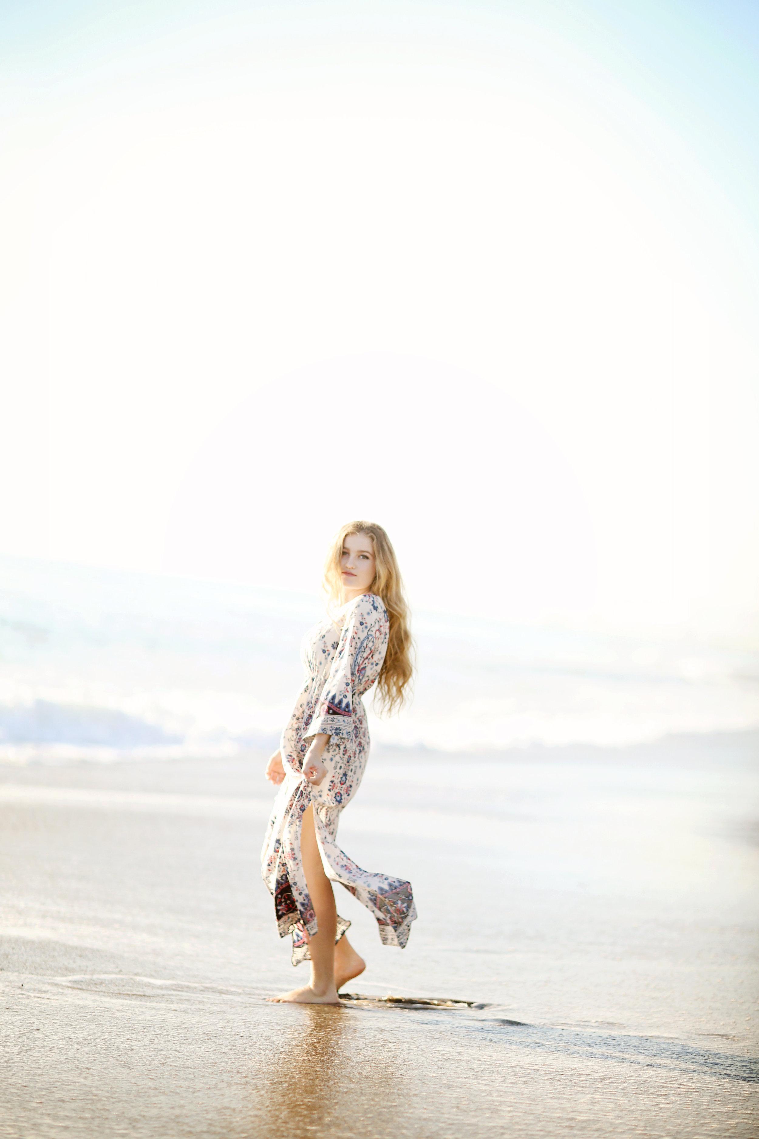Graduation portrait at the beach. Young girl with flowing dress and long hair.