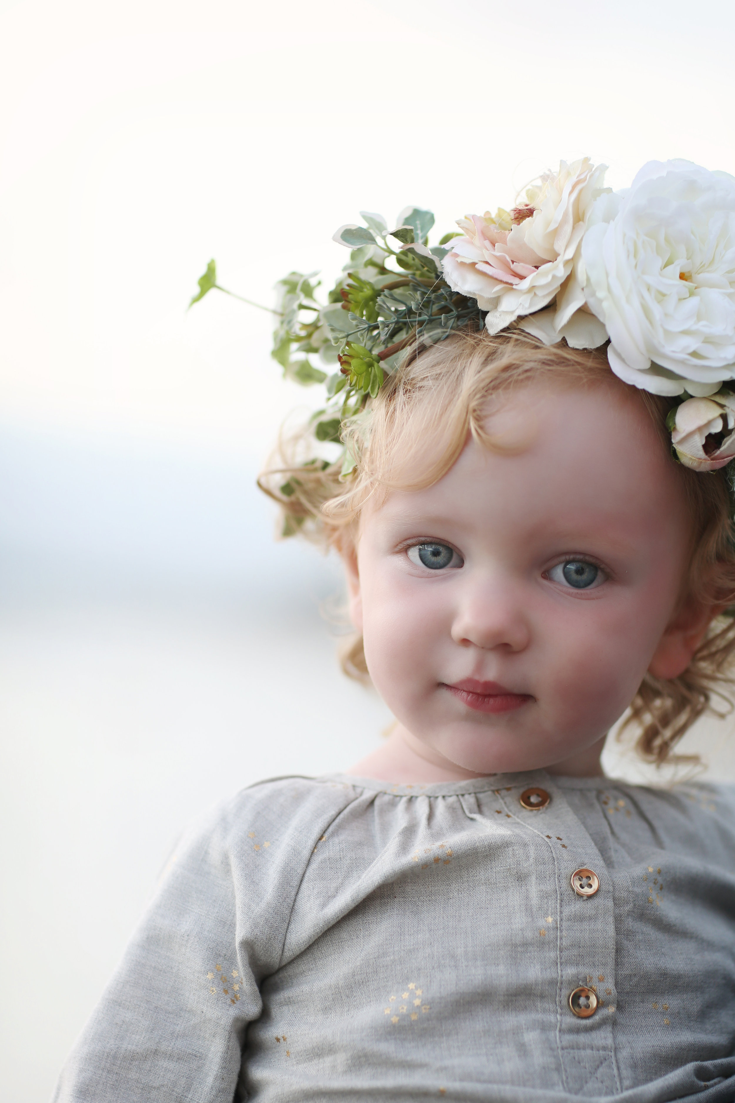 Toddler wearing a flower crown at the beach in orange county. Beach portrait of a baby.