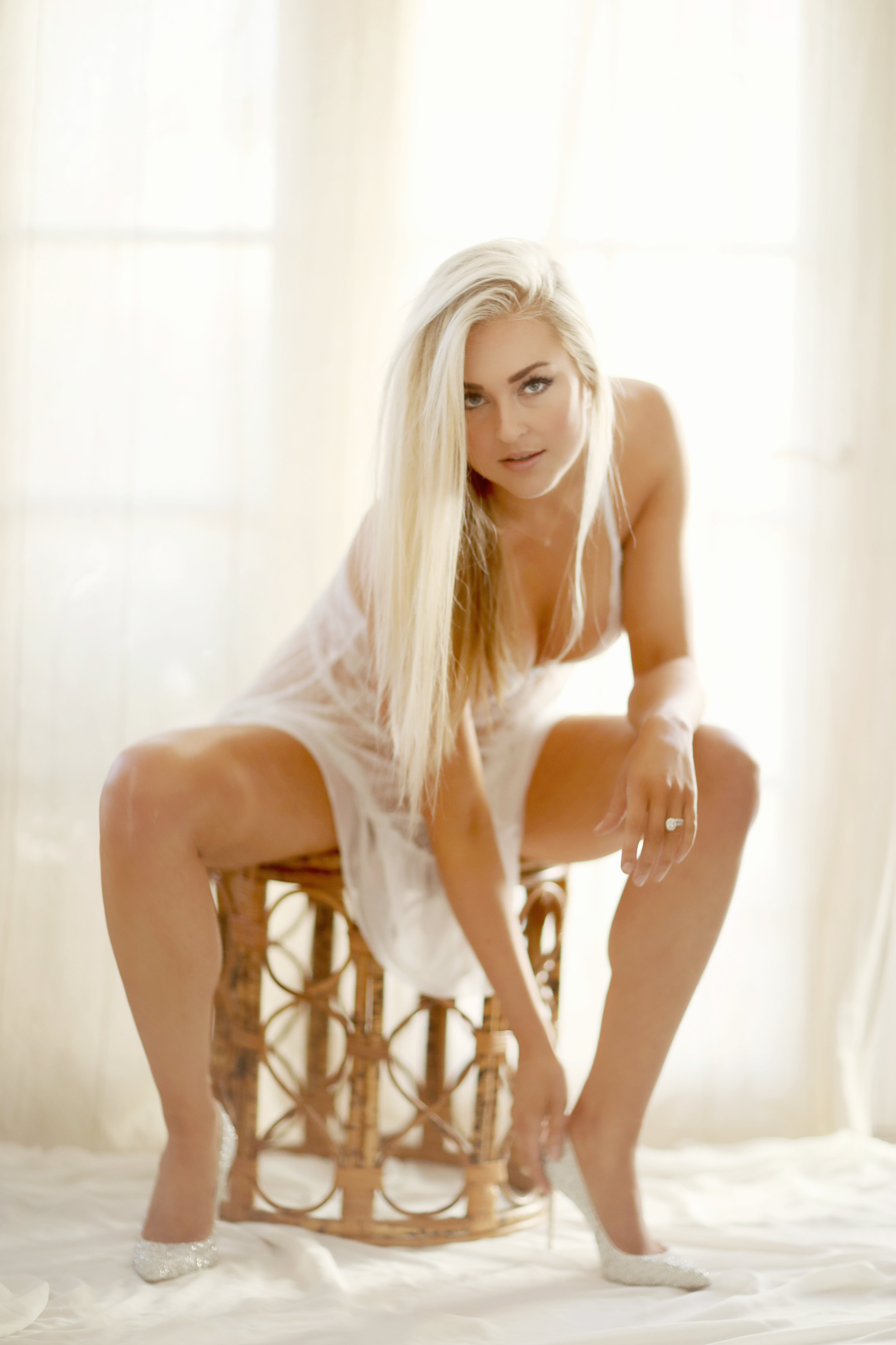 Blond long haired sexy girl sitting on a rattan stool in a boudoir photoshoot