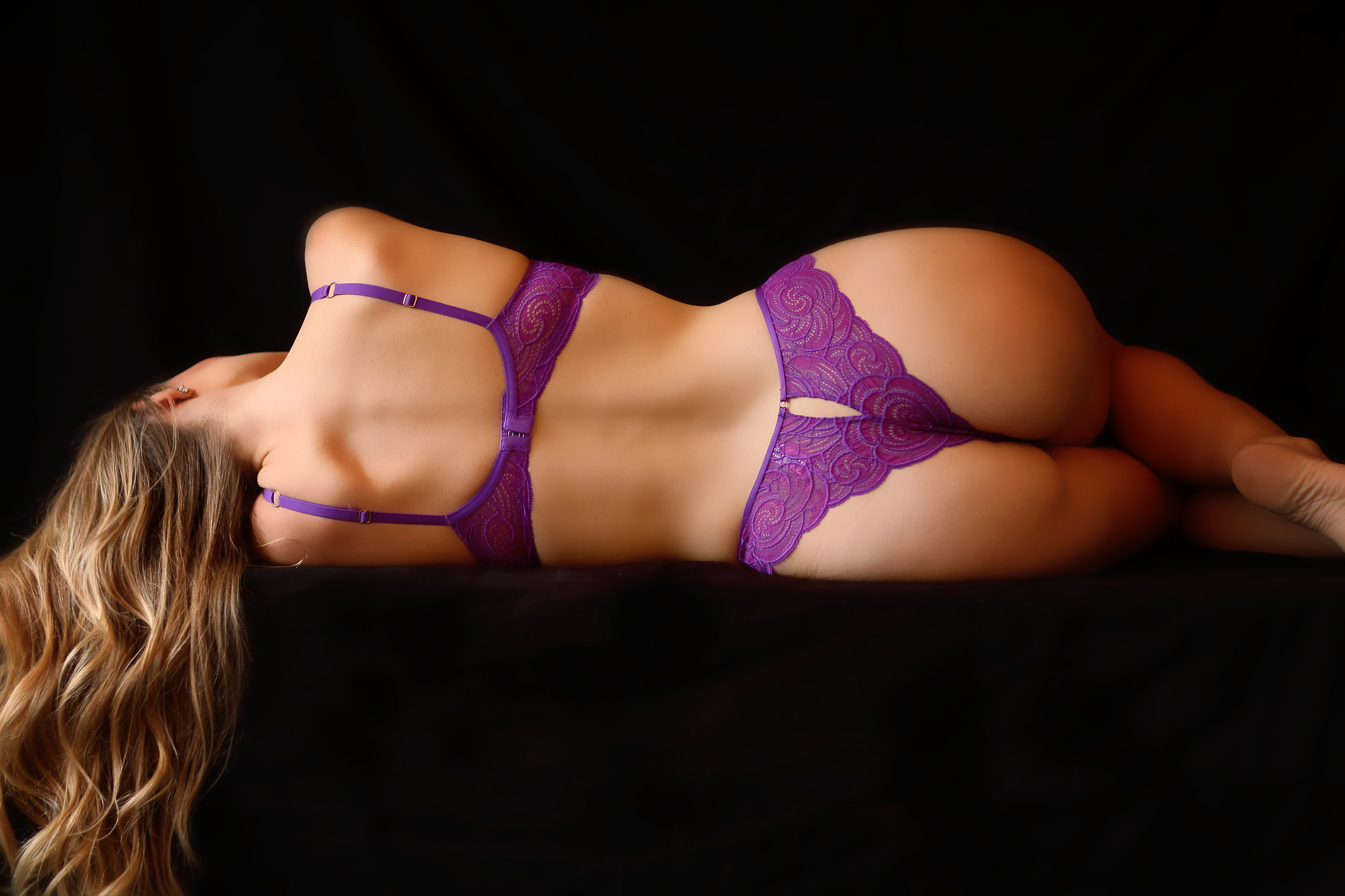 The back view of a boudoir portrait shoot of a girl wearning a sexy fushia thong and bra