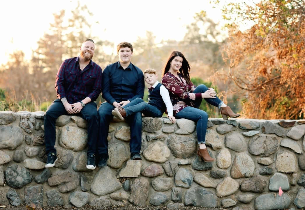 Family of four sitting on a rock wall in Orange County posing for a formal family portrait.  Organic and natural