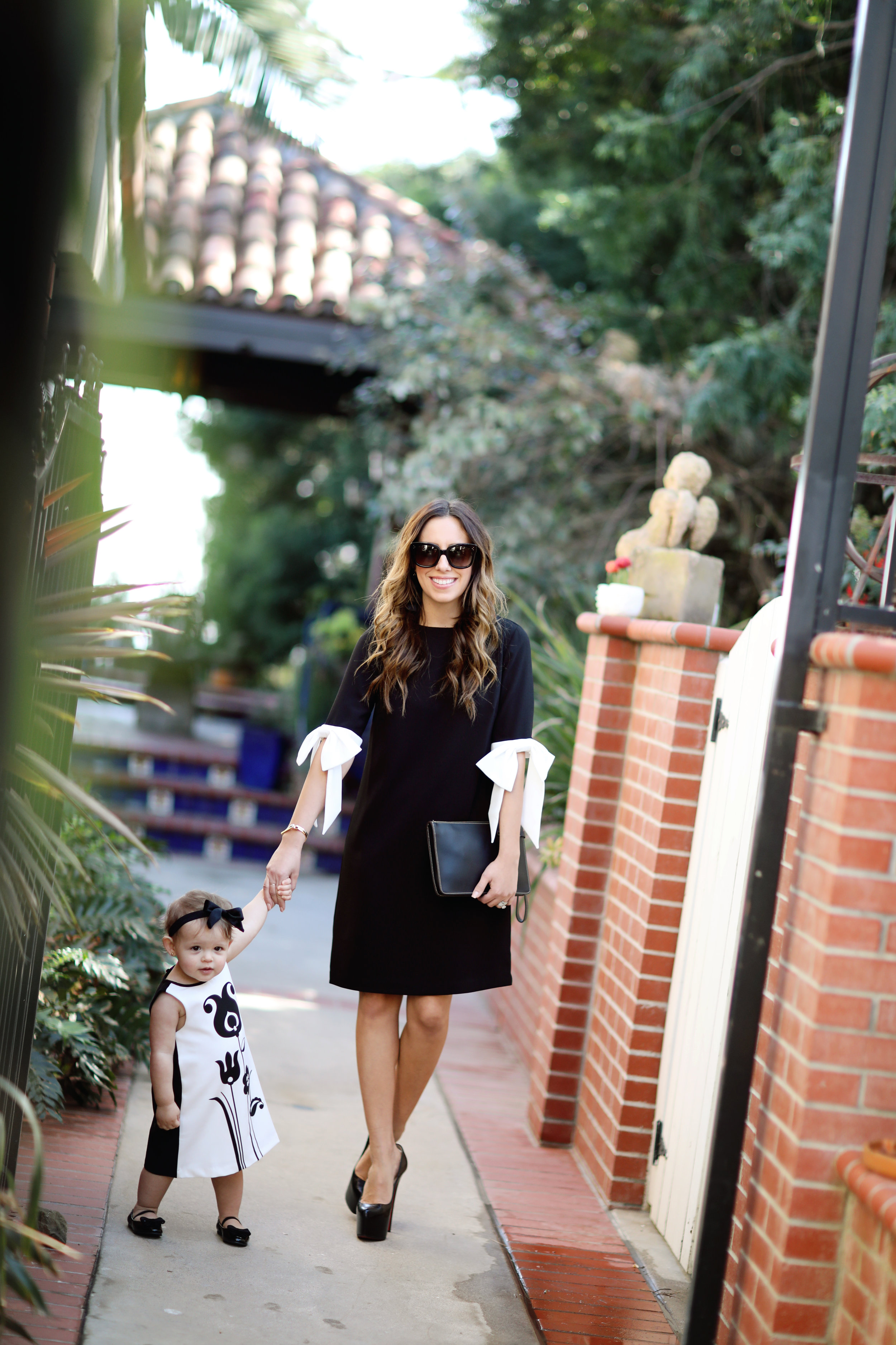 Mother and daughter walking down the side walk in black and white dresses. Fashion blogger photo.  Living in Style OC