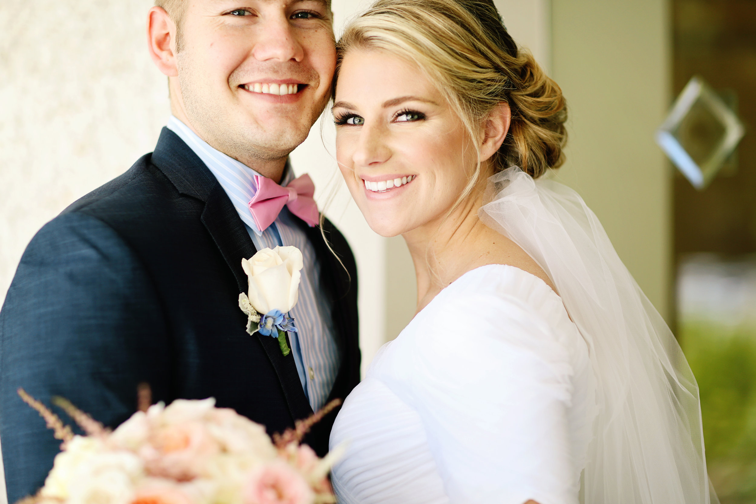 Groom wearing a pink bowtie with his young bride posing for a wedding portrait