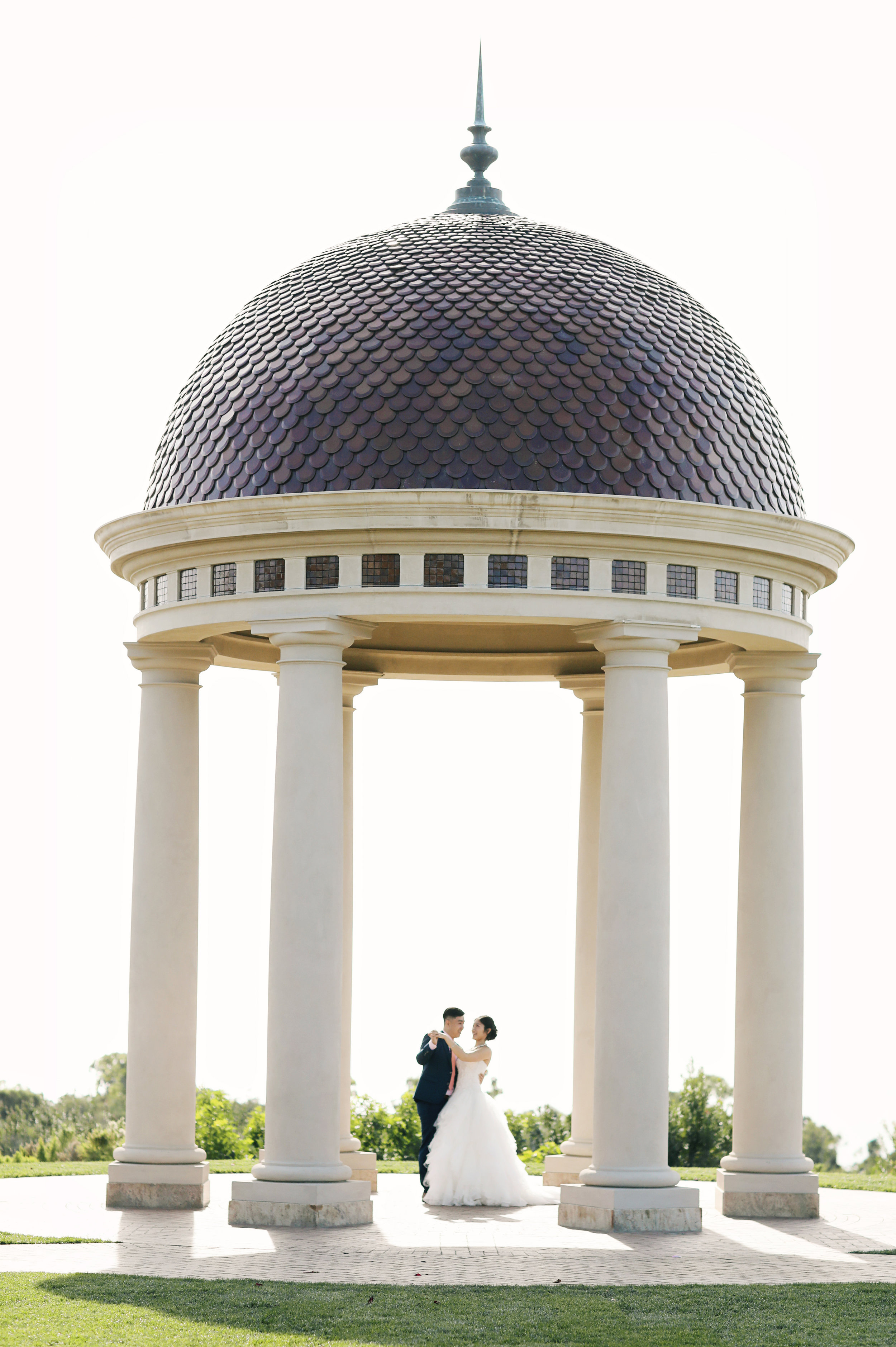 fine art photo of the bride and groom standing under the rotund at the famous  Pelican Hill Resort  in Orange County California