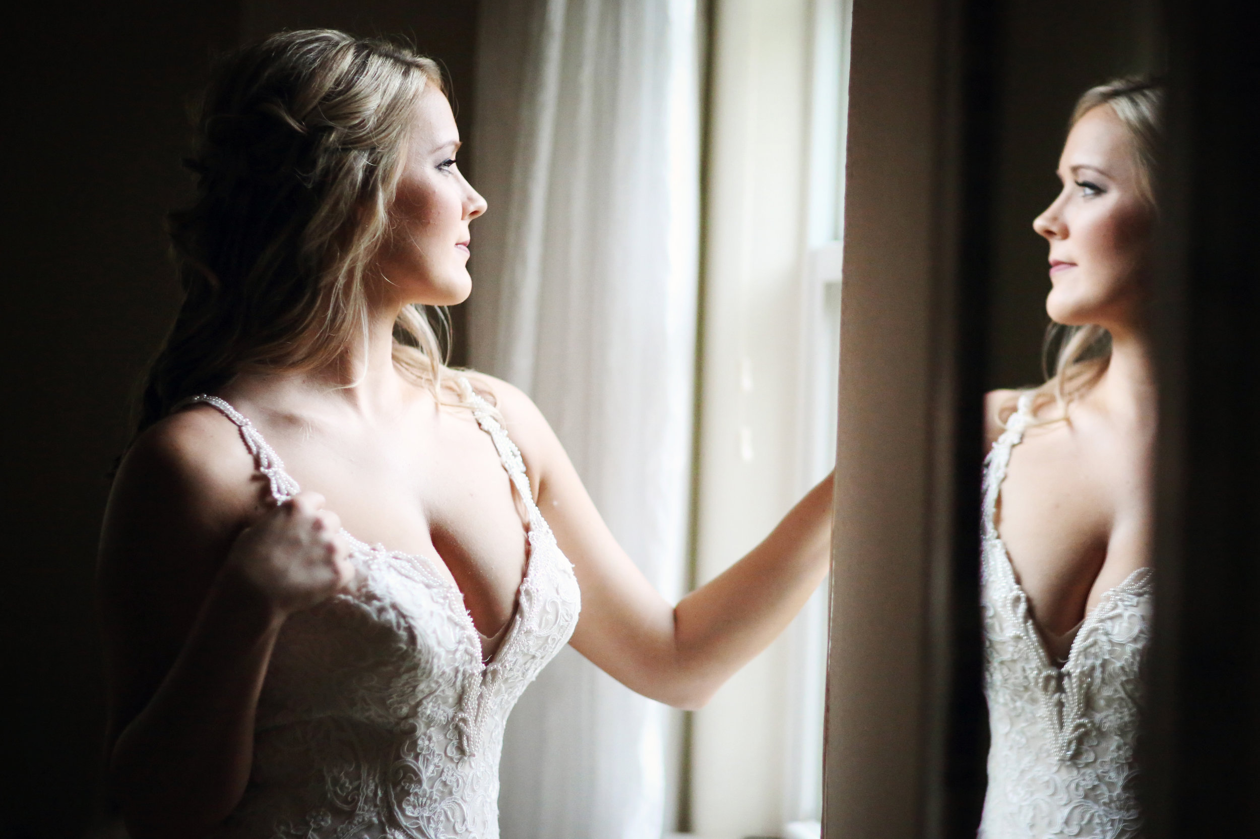 Great fine art photo of a bride looking in the mirror at her reflection.