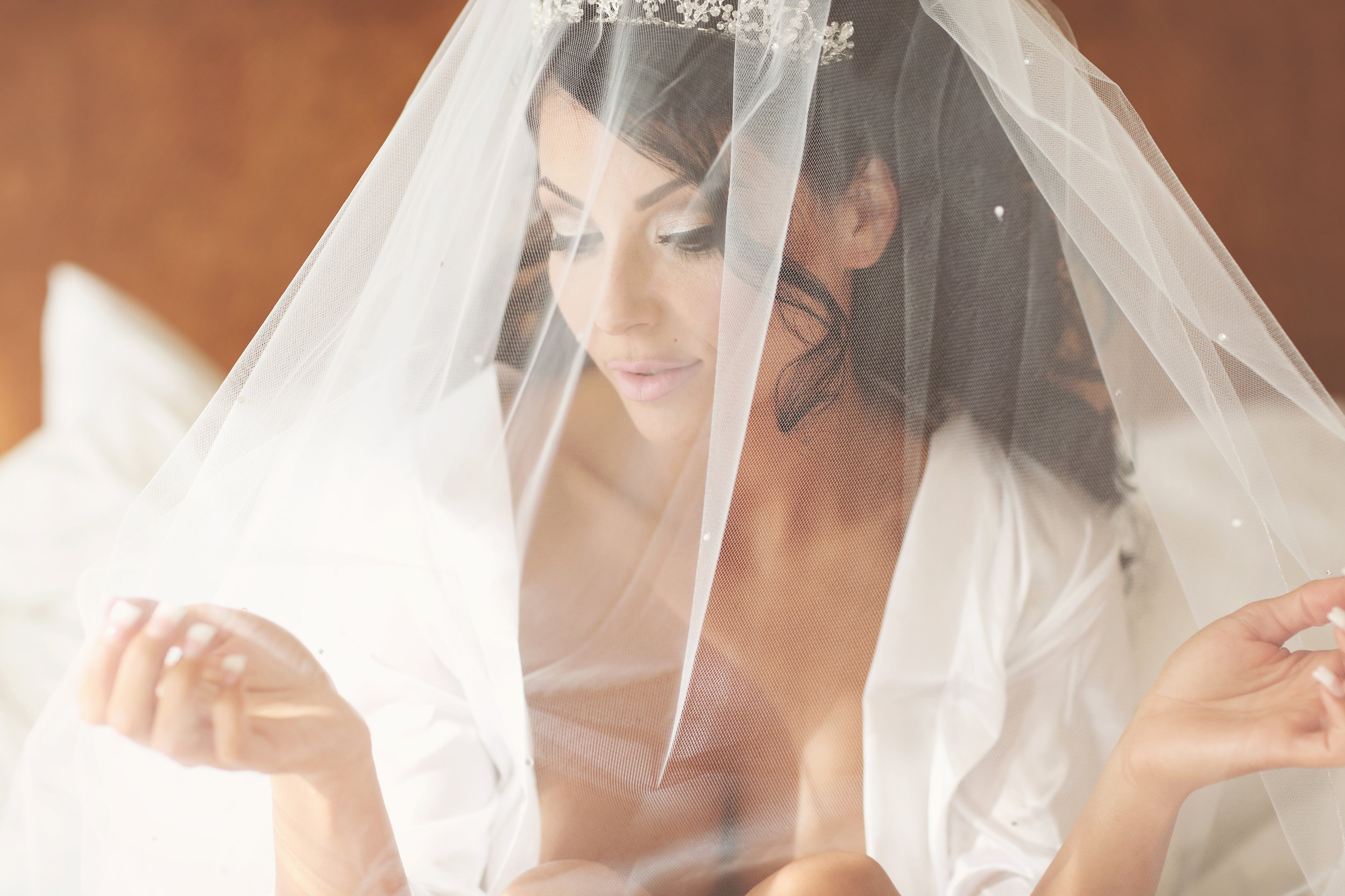 bride wearing a veil and crown doing a boudoir photo shoot