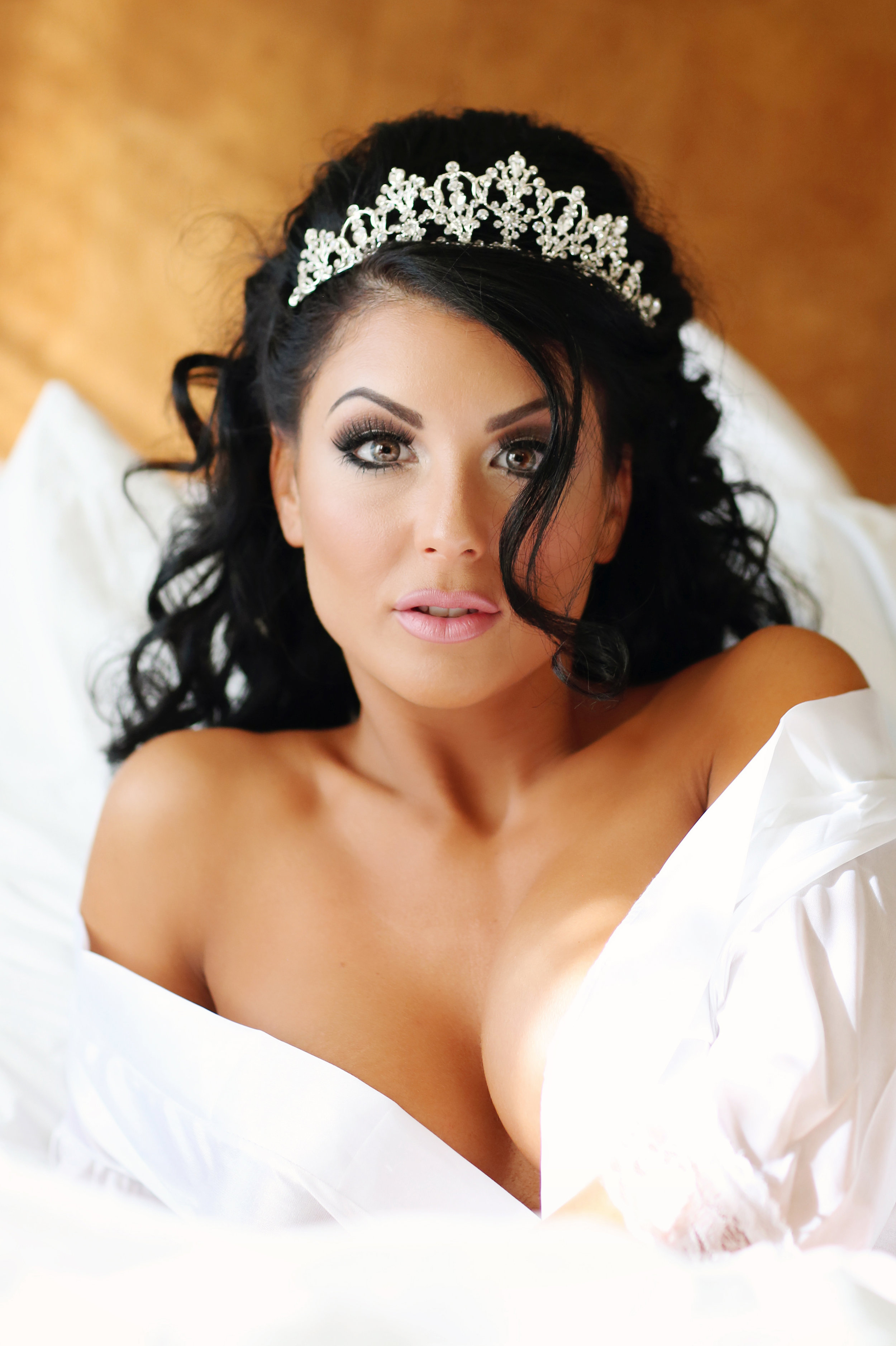 black haired model in sexy pose wearing a crown portrait.  Boudoir