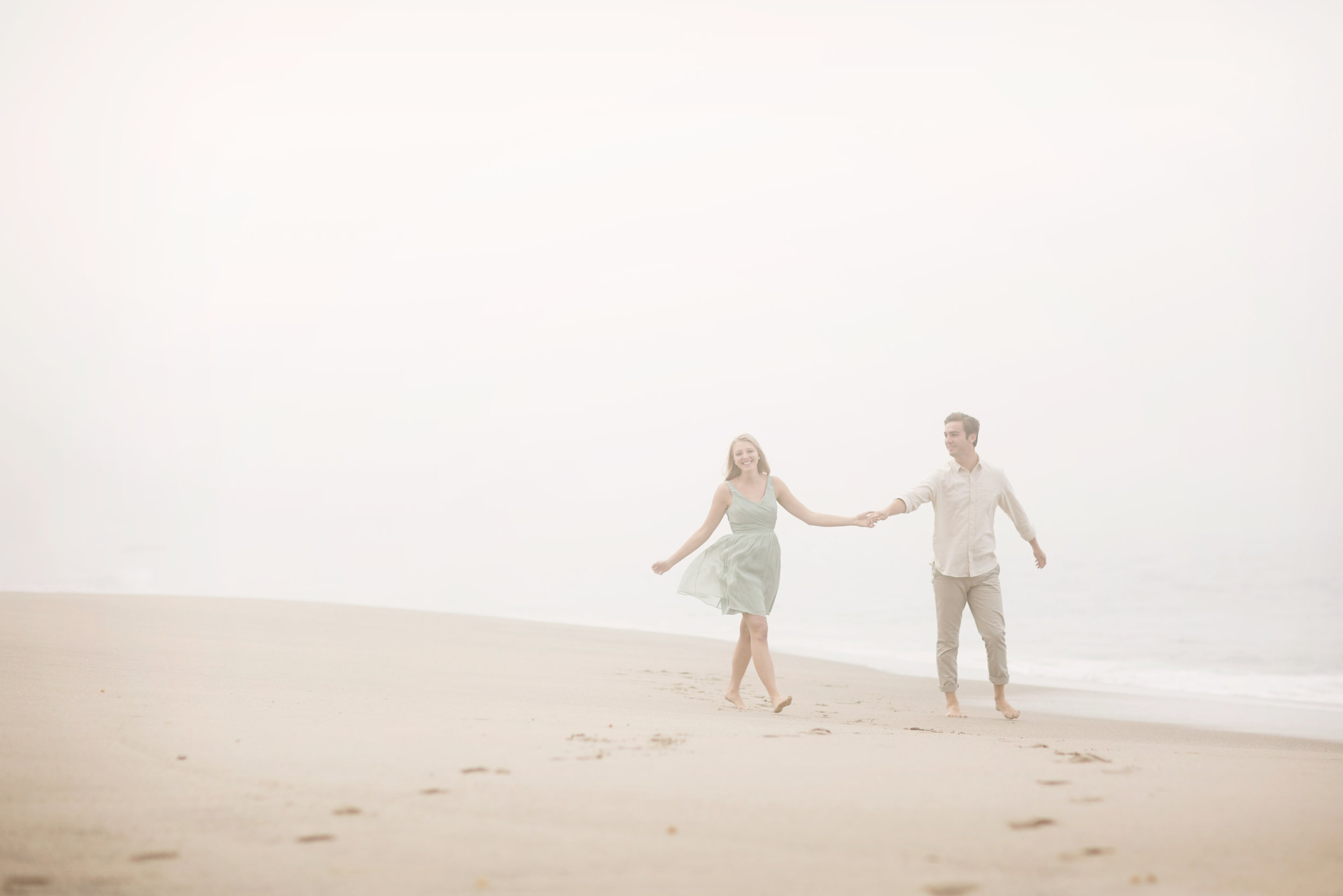 A foggy day at the beach makes the perfect beach portrait for this engaged Orange county couple.