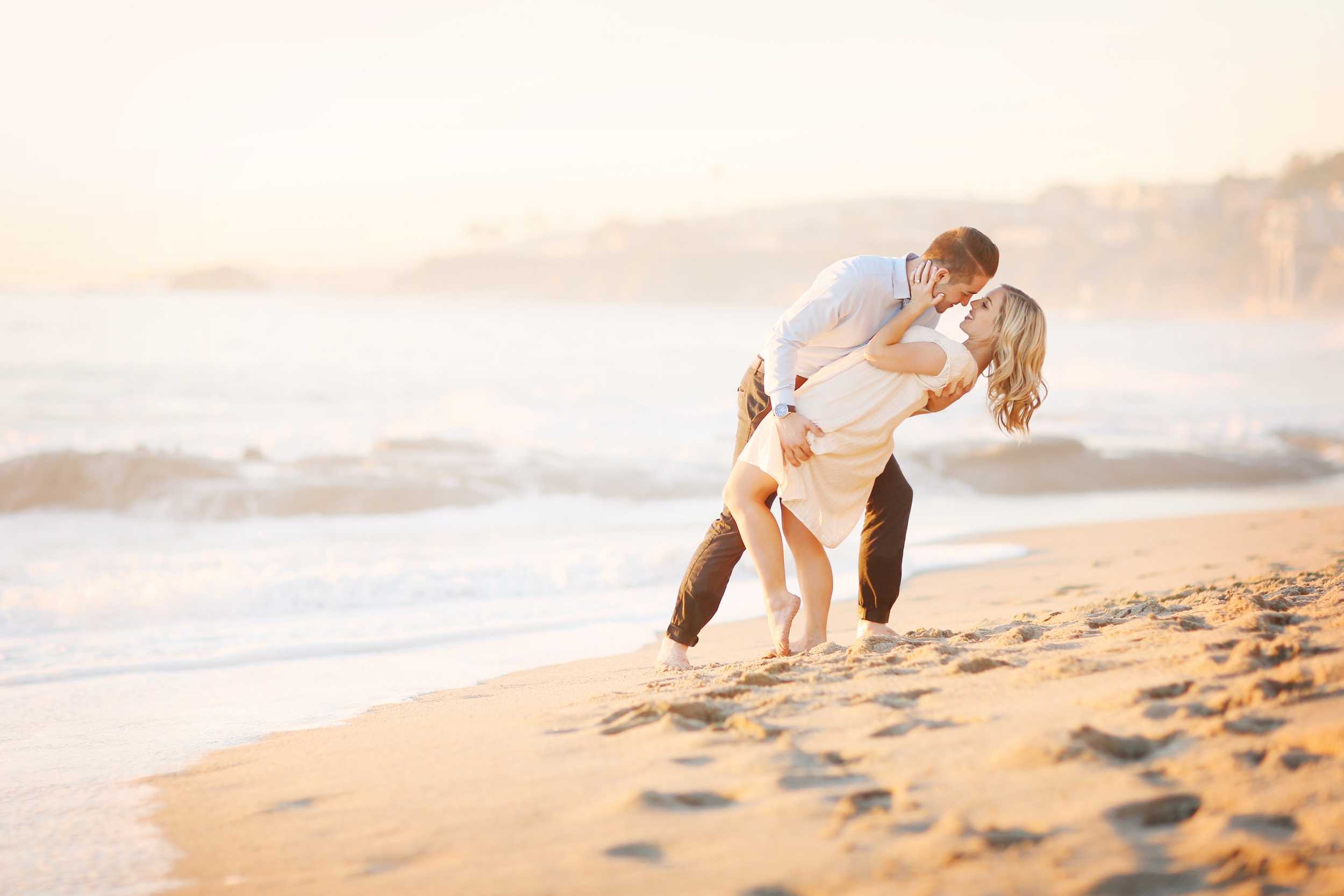 A young man tips a girl back as he goes in for a kiss at the beach in Orange County
