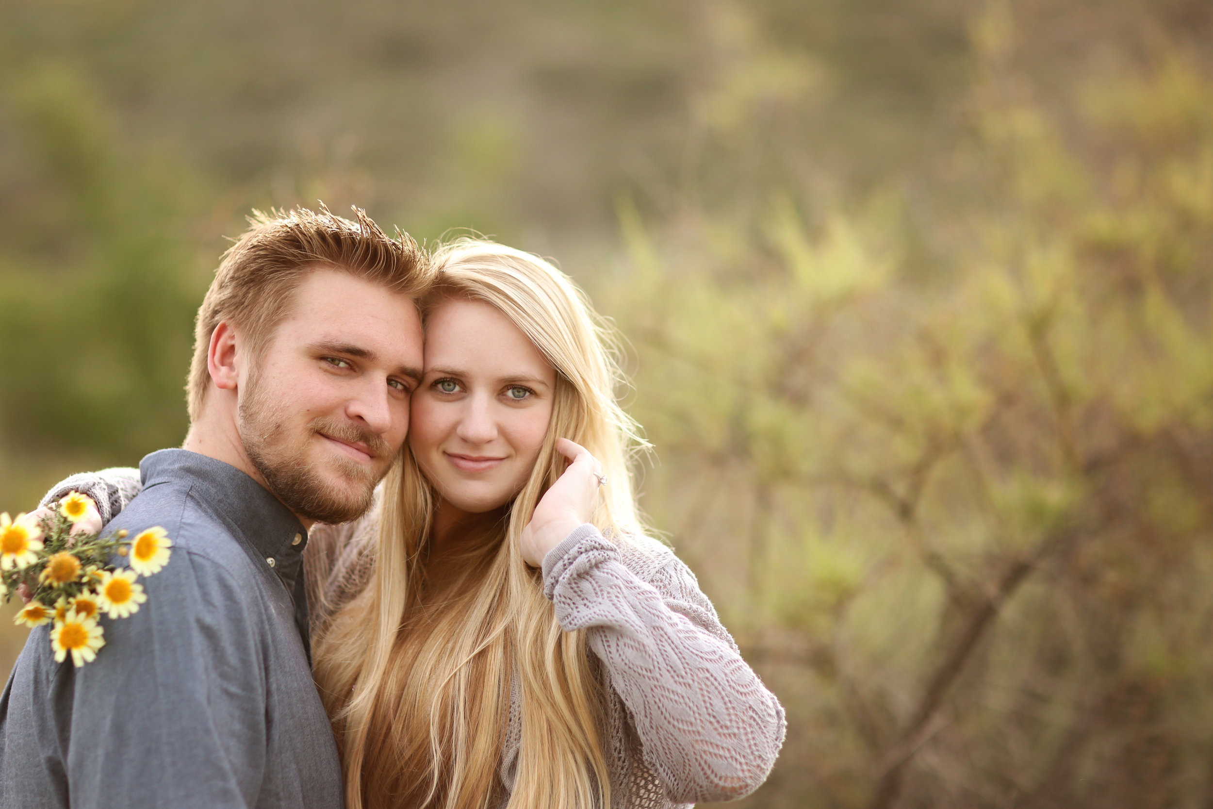 Future bride and groom in a beautiful field holding yellow flowers for their engagement photo. Orange County location.