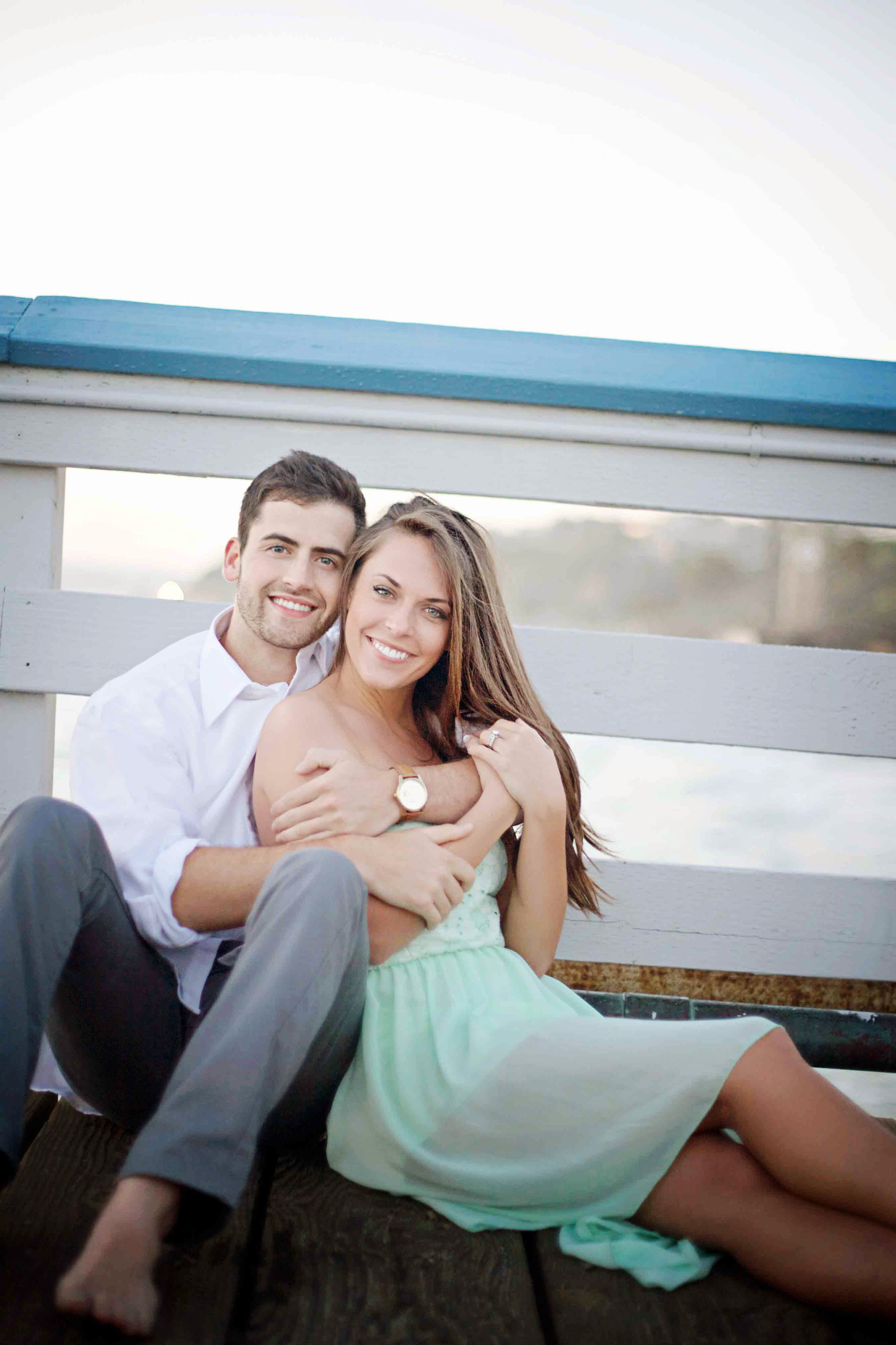 Couple sitting on the dock at the beach in Orange County posing for their engagement photo