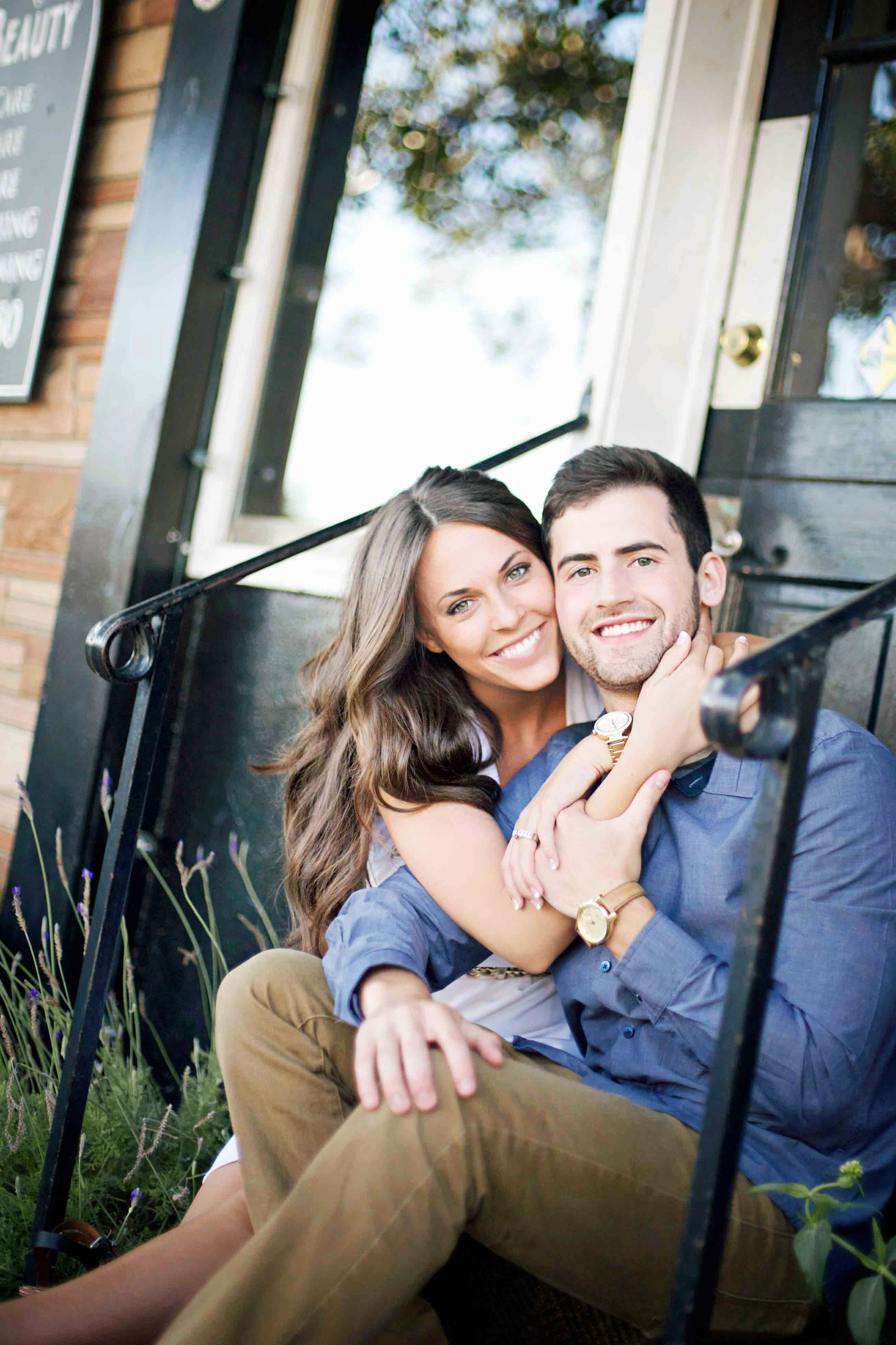 Couple sitting on the steps of an Orange County beach cottage posing for their engagement portrait.