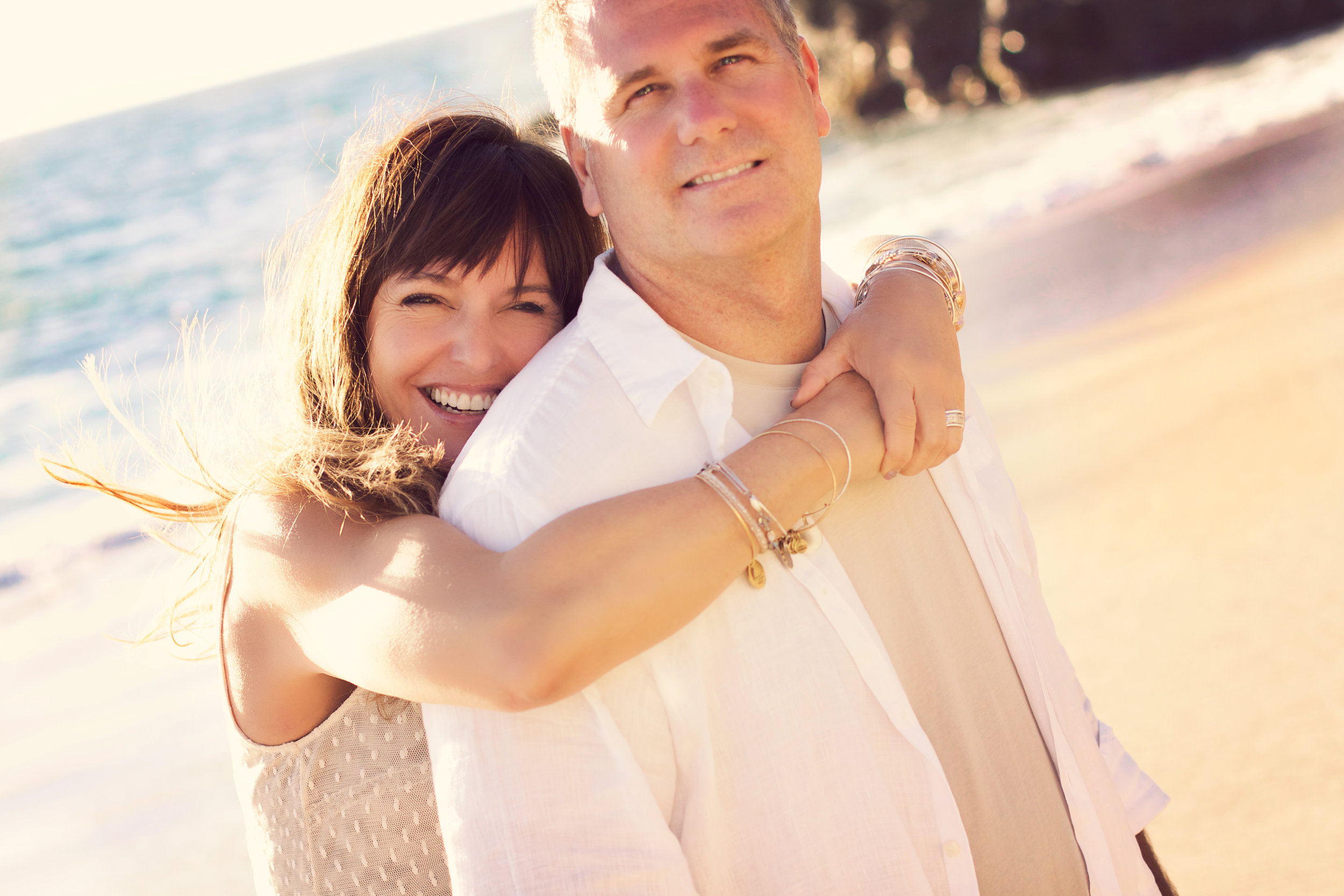Happy couple posing at San Clemente Beach in Orange County for their engagement portraits. Natural and organic smiles as the wind blows.