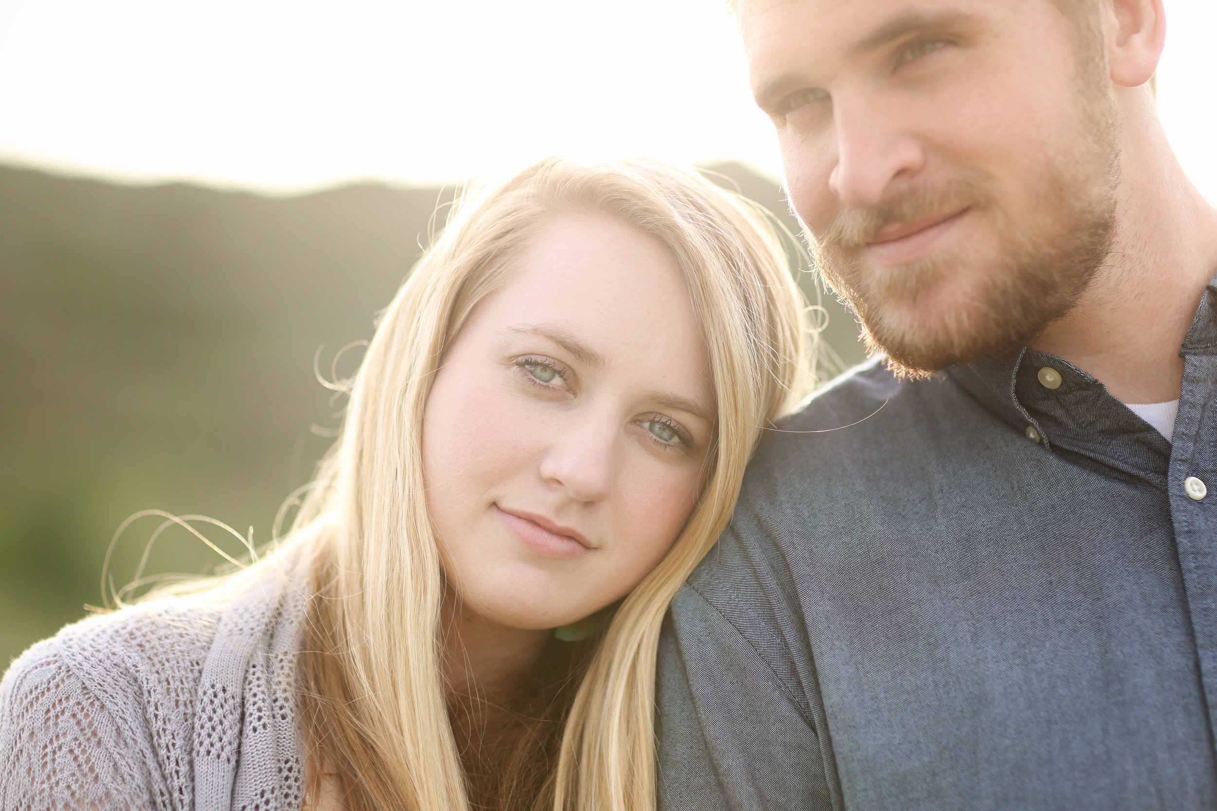 Girl with content look on her face leans her head on her fiance posing for her engagement photos.