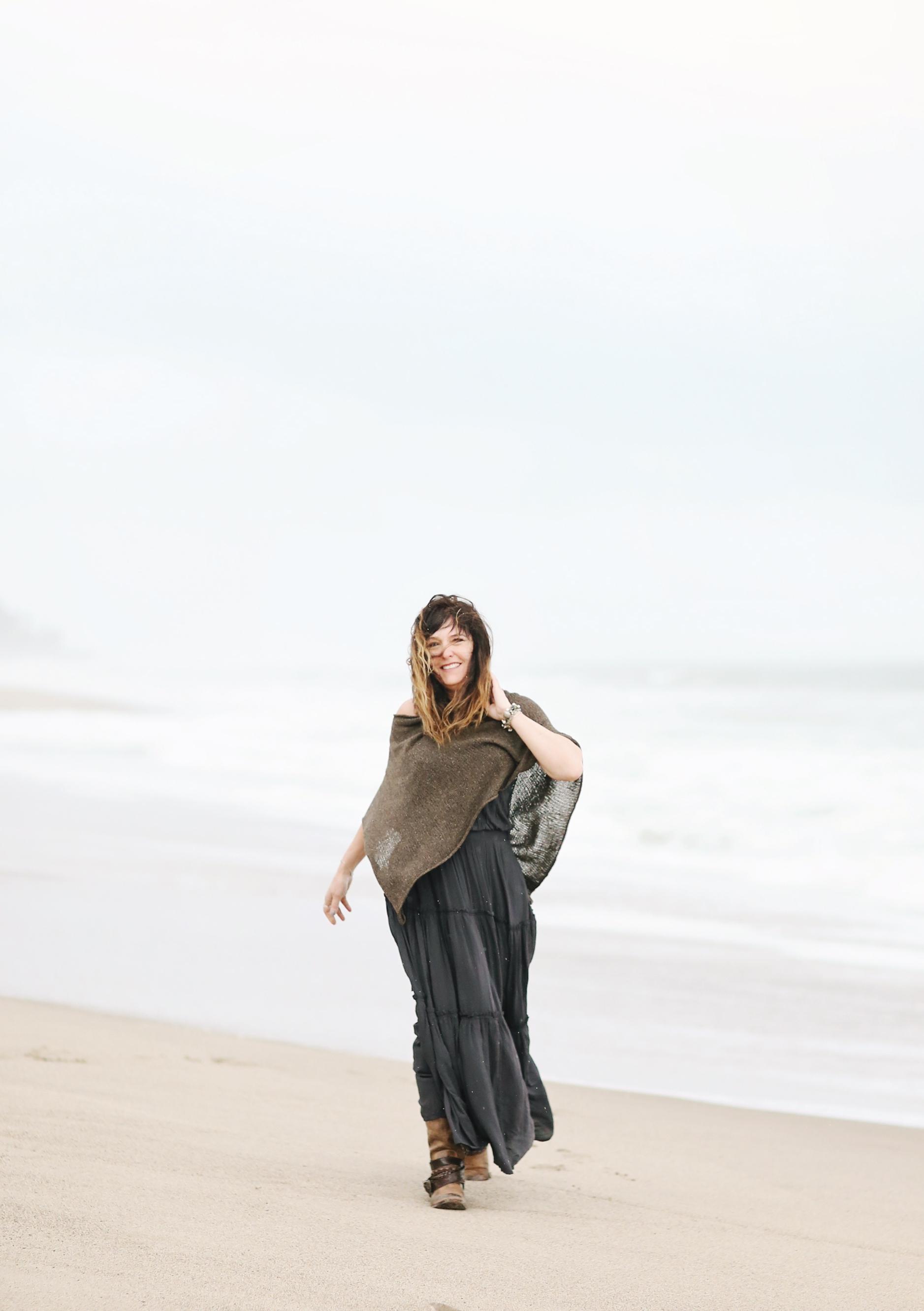 Fine art image of woman walking on the beach in the breeze. Beach portrait.