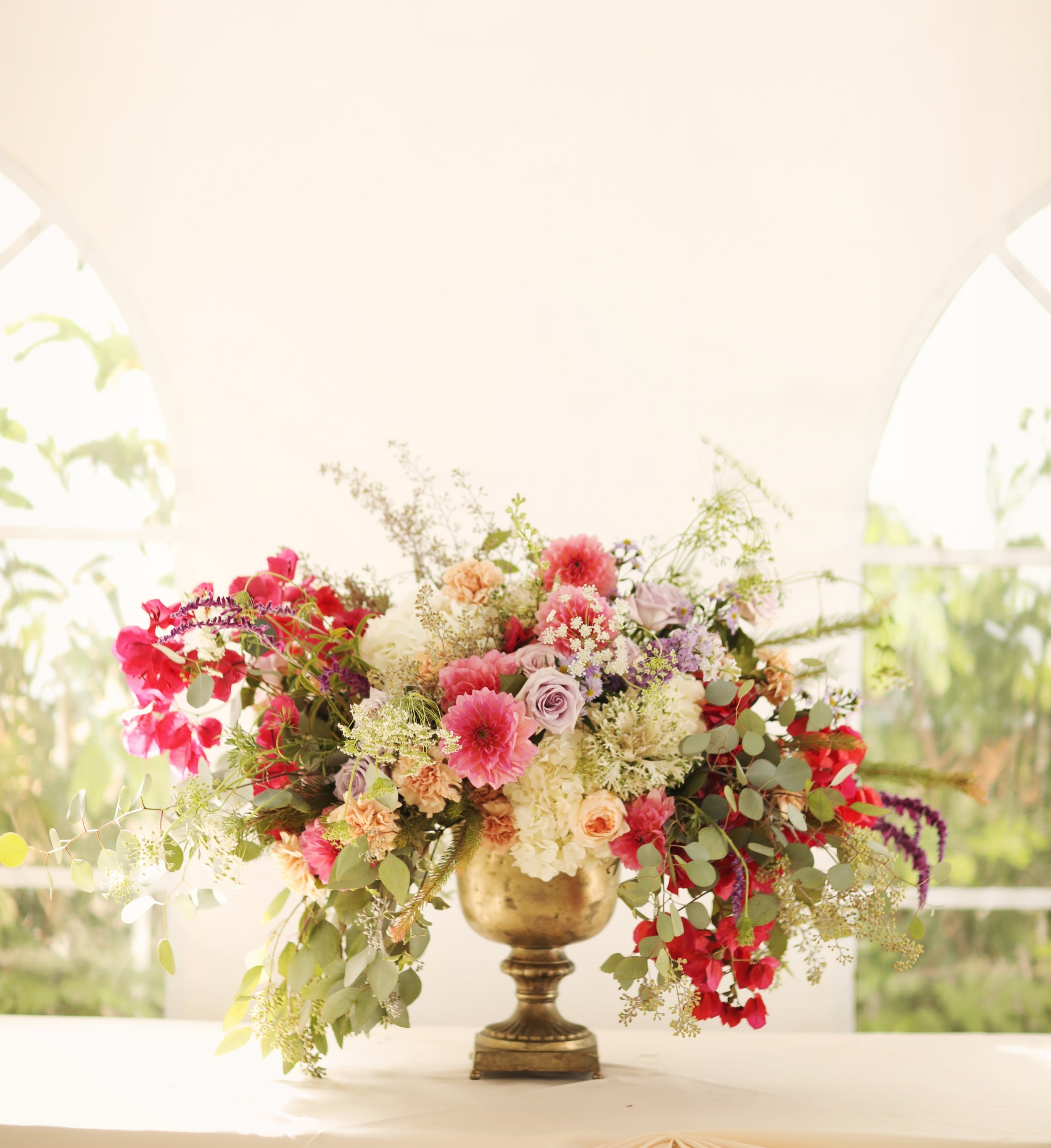 Roses and bougainvillea are the subject of this wedding photo. Reception floral arrangement by Bleudog Floral