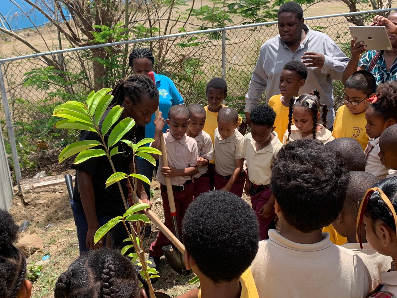Jahnai Caul and Akeem Leonard of Greencrete VI plant a Caribbean Cherry tree and Soursop tree with students at the Robinson O'Neal Memorial Primary School.