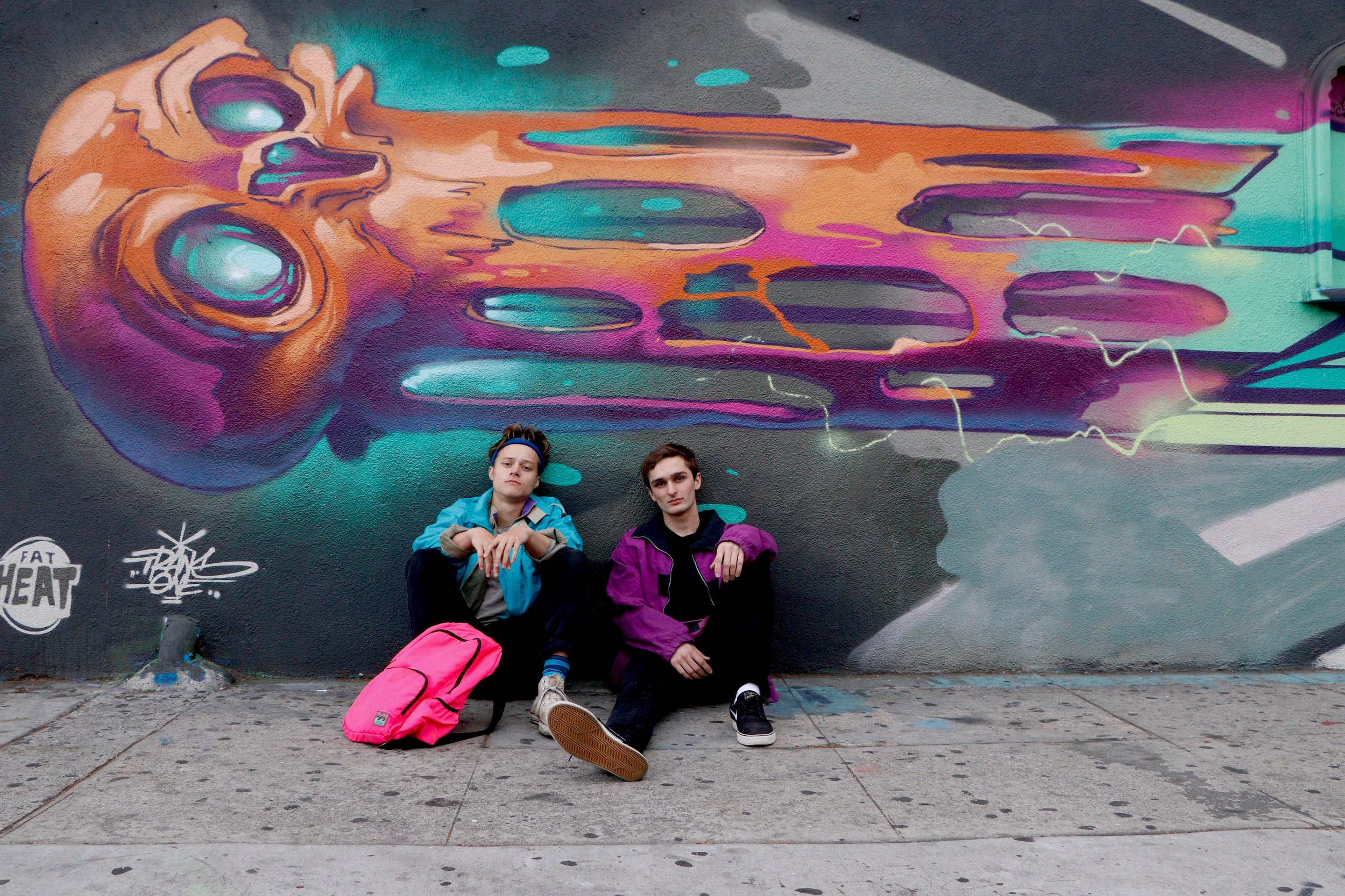 Rudy Pankow (left) and Drew Gabriel (right), playing Joey and Marvin, pose in costume next to some street art.