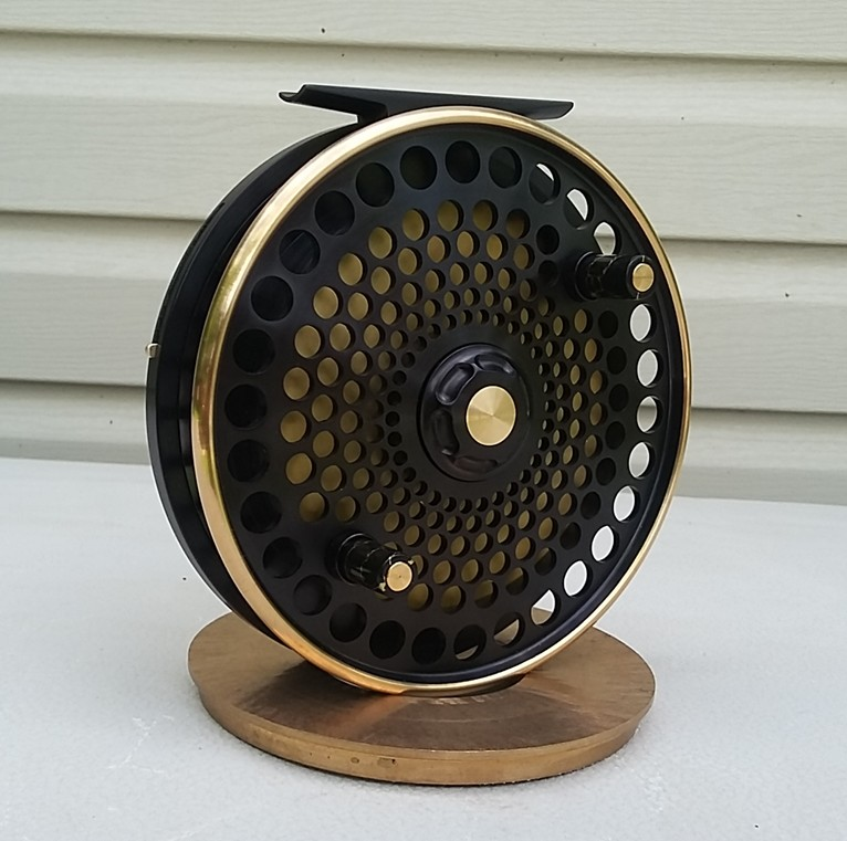 "This is a special version of the Rainmaker, called the Rainmaker Custom. It has 6 rows of holes and a shallow spool of 1/4"". We make only a few of them each year. The one in this picture has an optional drag knob, the reel is normally fitted with the flat spool cap. As it happens this one is right hand wind but like all our reels they are available in both LHW and RHW. The handles shown are very nice but we can no longer obtain the black/gold material. It is available in 4.6"" and 5"" in a variety of colours and the price for either size is $1400 Canadian, shipping extra and it comes with a black zippered leather pouch. There is an optional hand made leather case available."