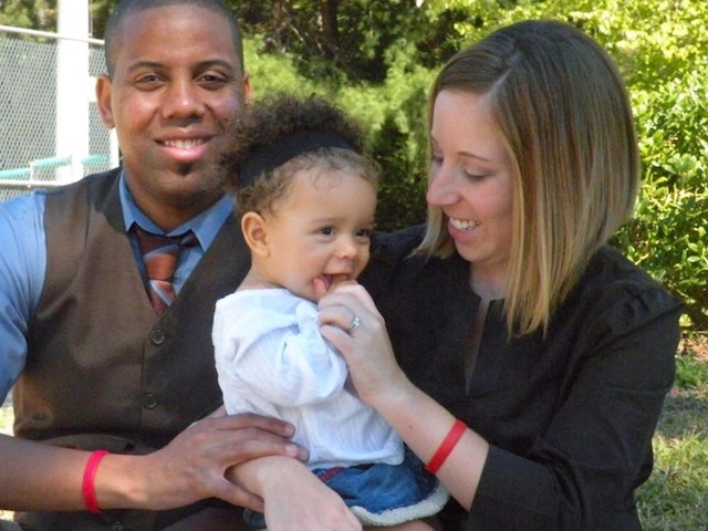 Holding their daughter, Cathy and Marcus Harris wear Life Bands—a daily reminder to pray for life (Photo: Harris Family)