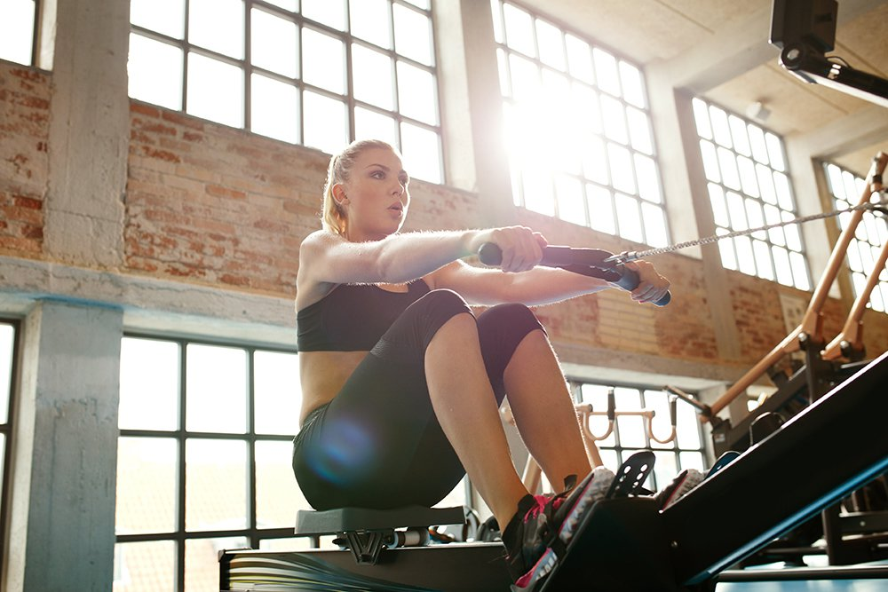 woman working out on rowing machine at gym