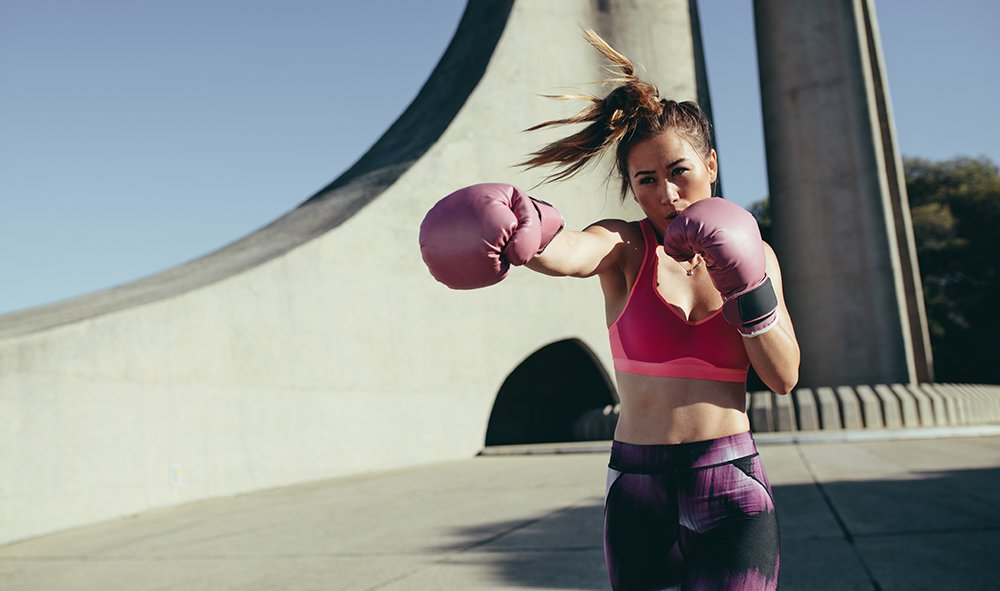 woman shadowboxing with pink boxing gloves outdoors