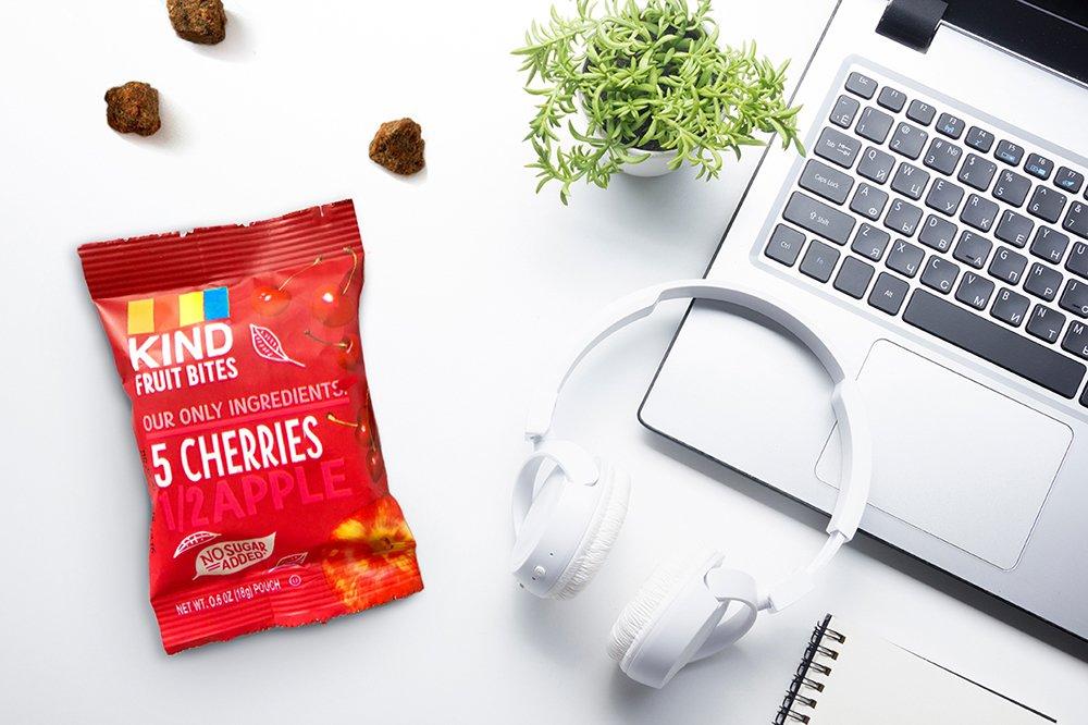 desktop with Kind Fruit Bites cherry apple diet snacks headphones macbook laptop desk plant