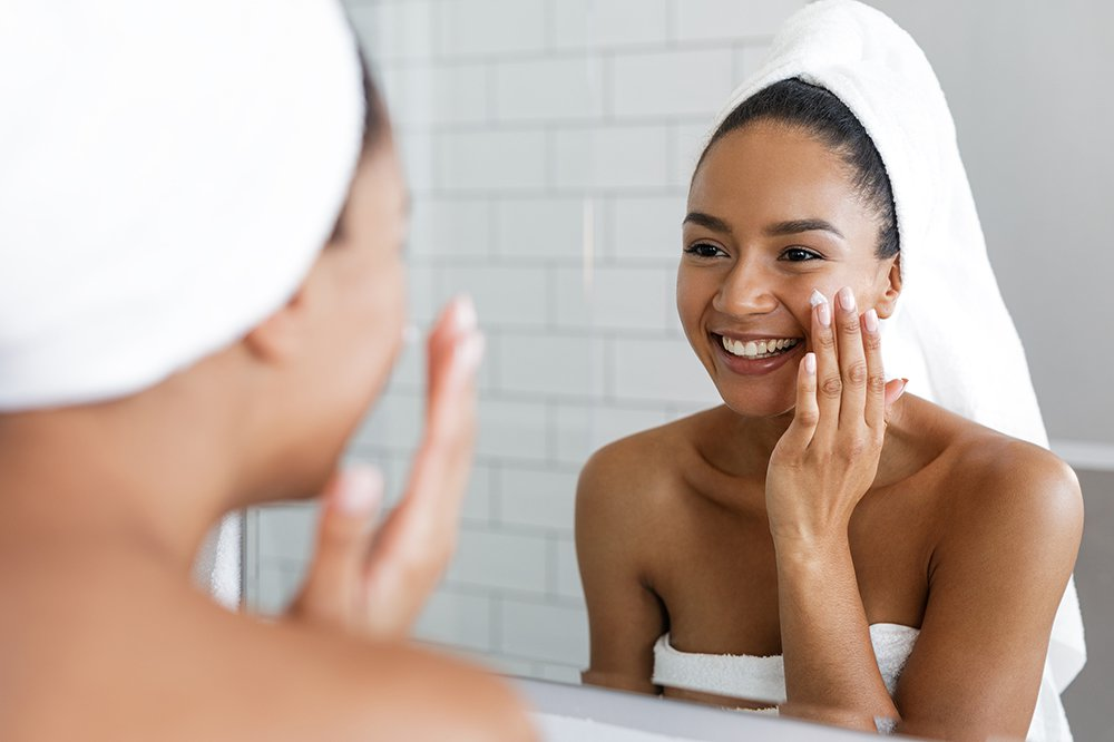 woman applying skin care product after shower