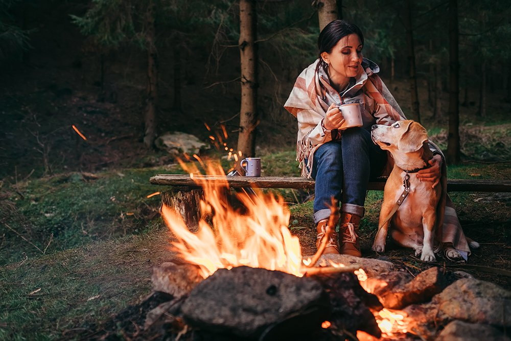 Woman and dog sitting by campfire in the woods while drinking from a mug and wearing a blanket
