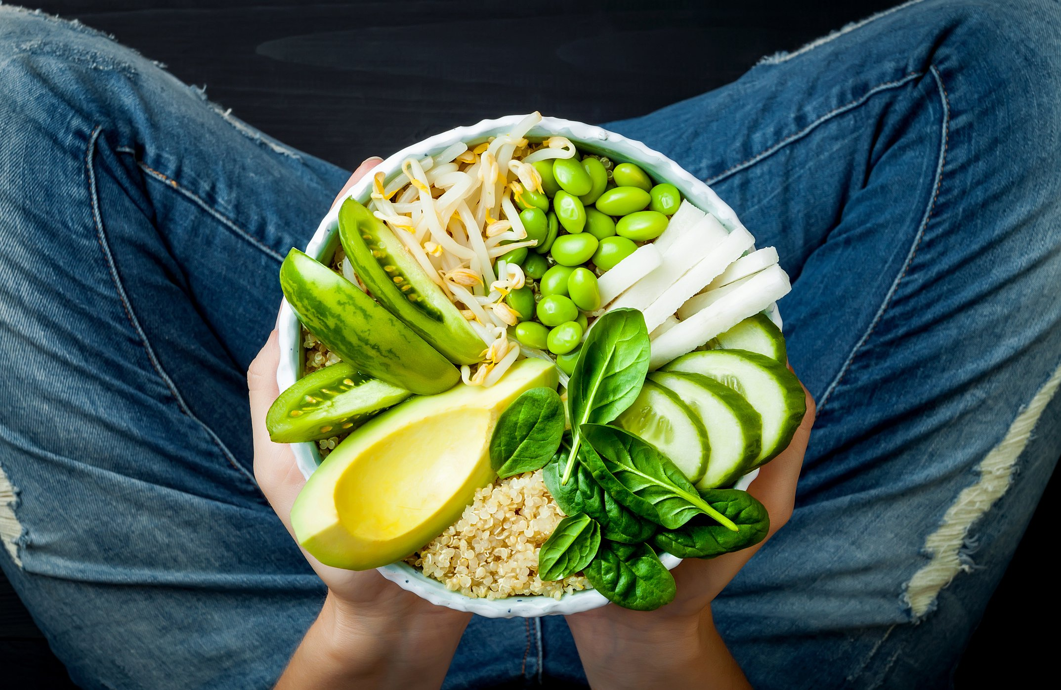 Vegan bowl full of quinoa avocado bean sprouts cucumber soy beans and spinach