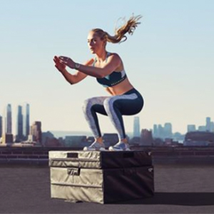 Woman with ponytail doing squats on a city rooftop with skyline in the background
