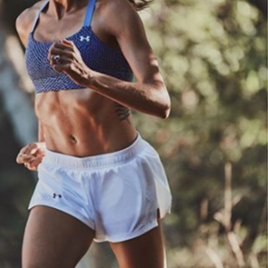 Woman running in white Under Armour running shorts and blue Under Armour sports bra