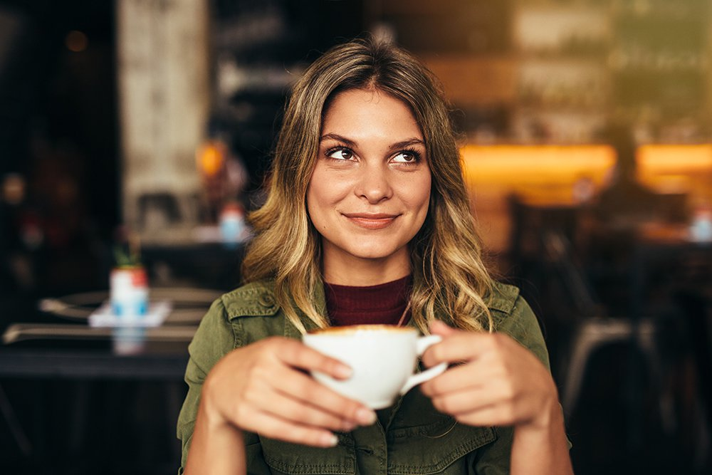 Woman with closed mouth smile drinking cappuccino in white mug