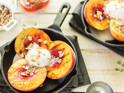Grilled peaches with oats and cream in cast iron skillet