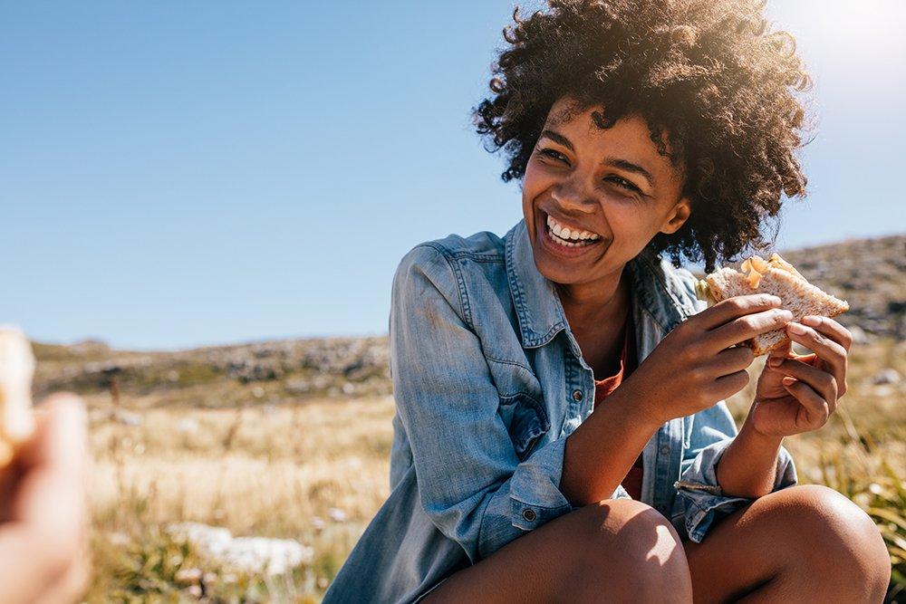 Woman wearing jean jacket eating sandwich in the desert