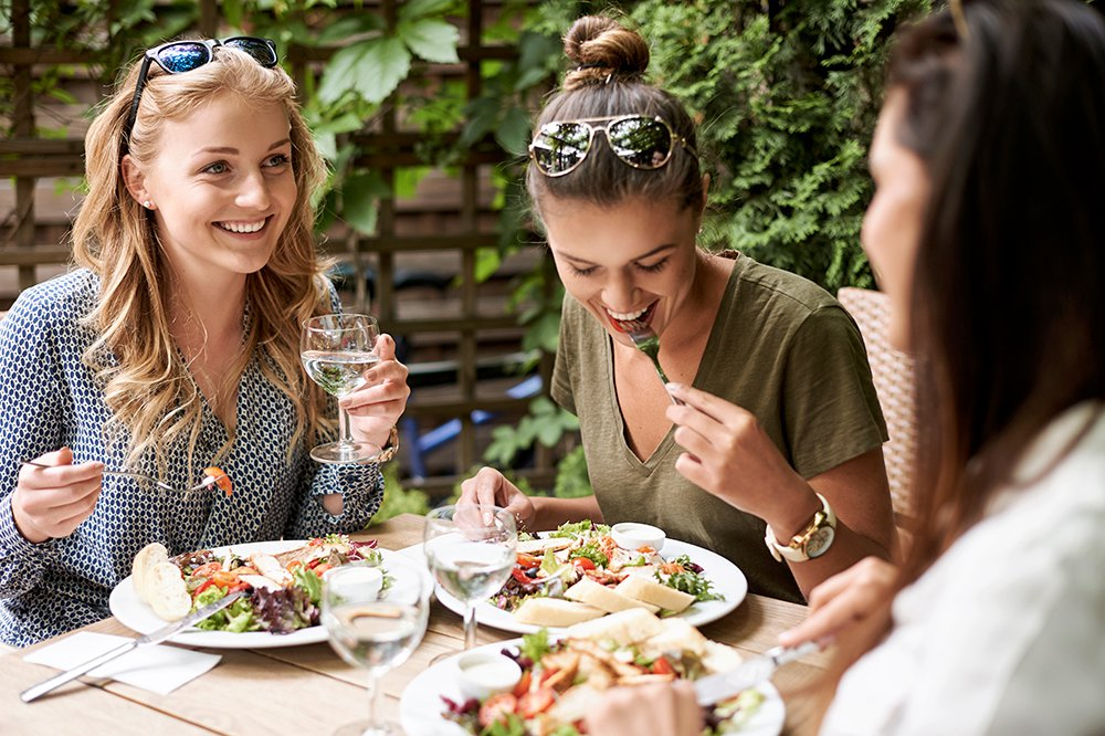 Women with sunglasses on their heads eating salads outdoors