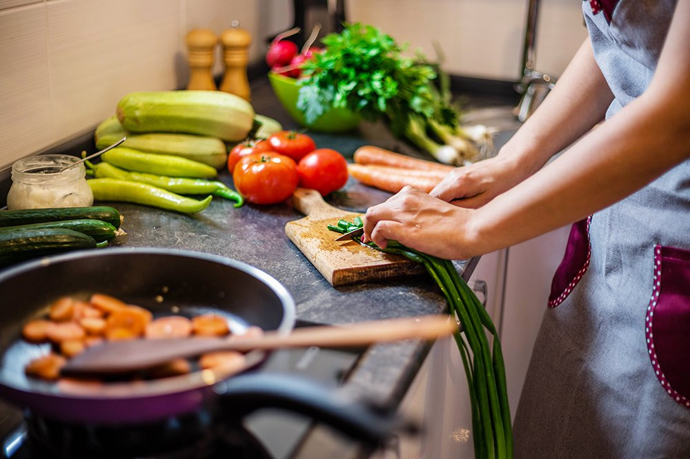 Woman's hands chopping fresh veggies while cooking carrots