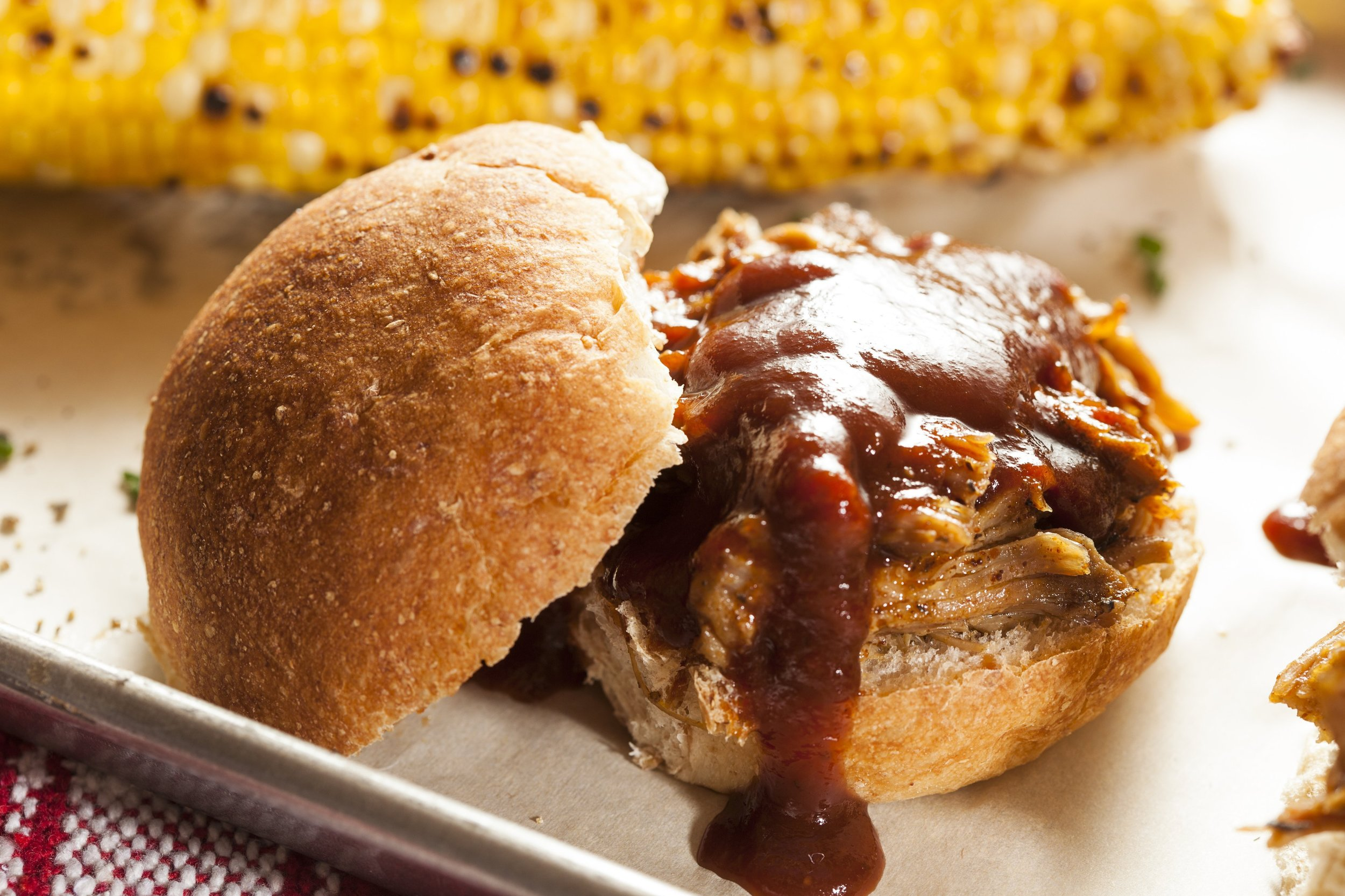 Barbeque chicken sandwich on a roll served with corn