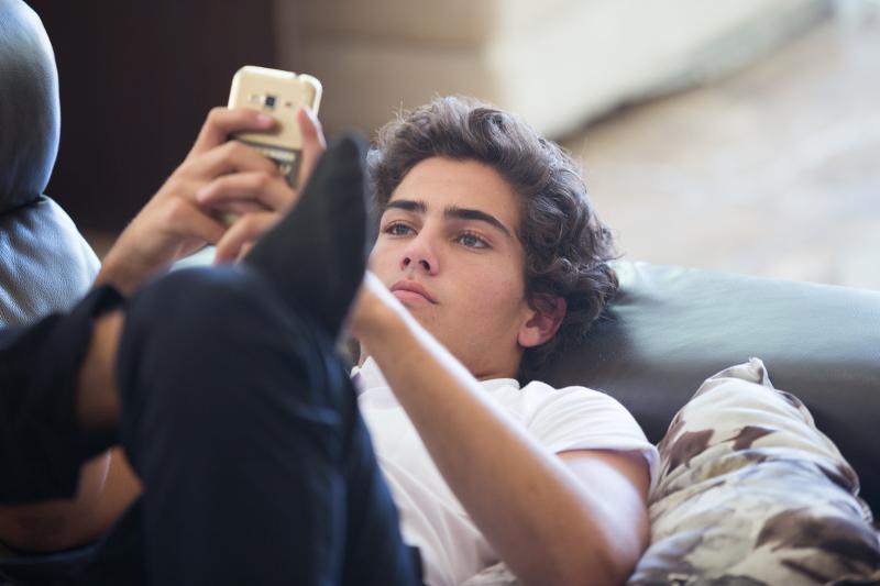 Bored teenager using mobile phone