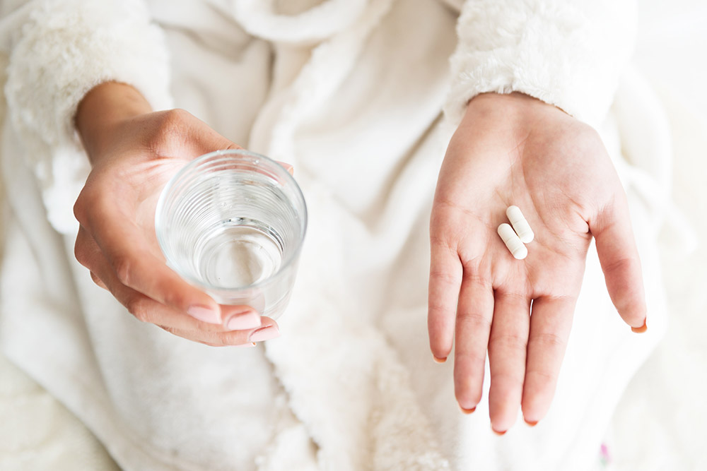 Woman-holding-vitamins-and-water.jpg