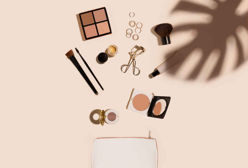 beauty products still life coming out of makeup bag with palm leaf shadow on pastel background.jpg